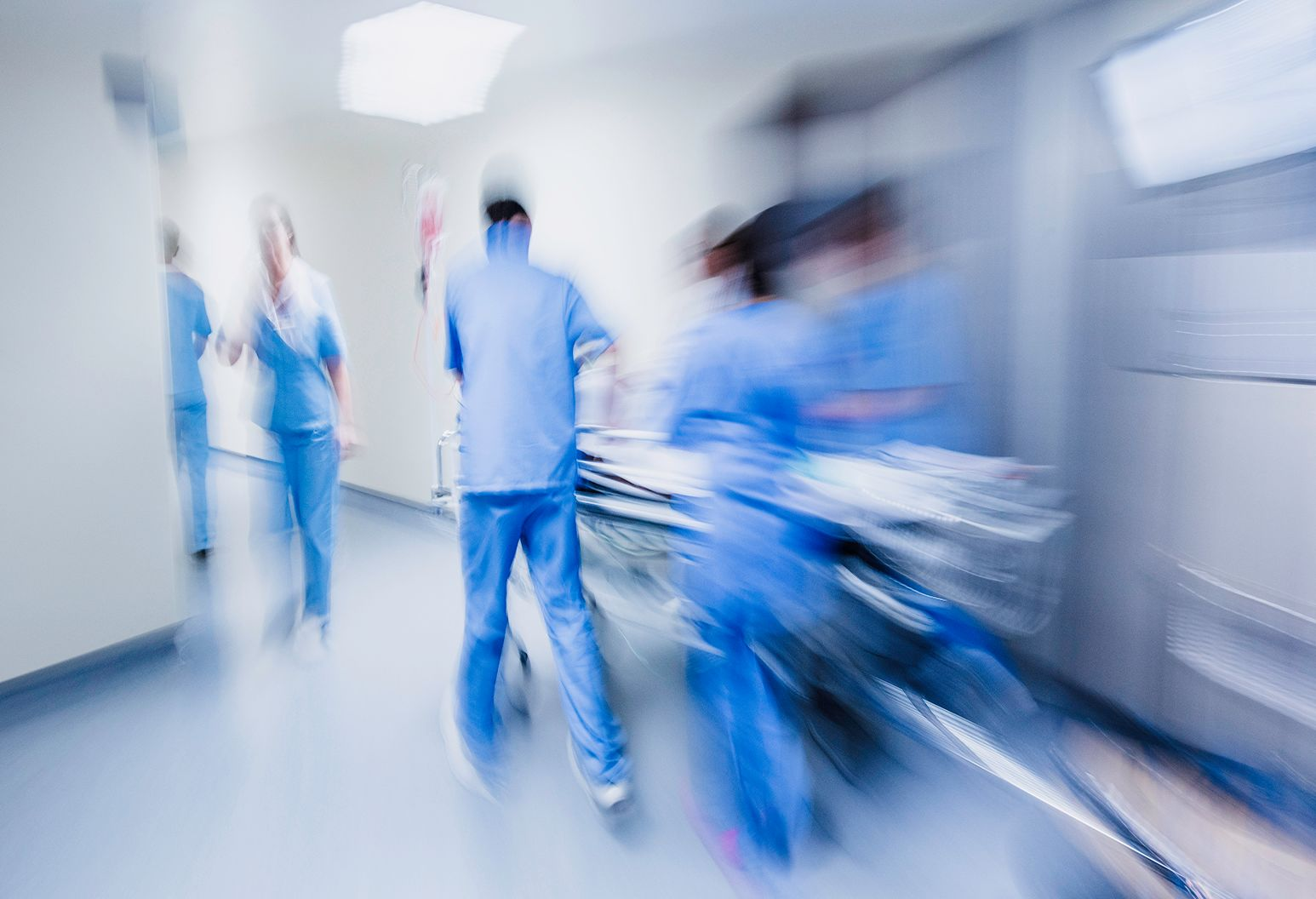 A blurry image of an emergency room staff quickly wheeling a patient down the hallway.