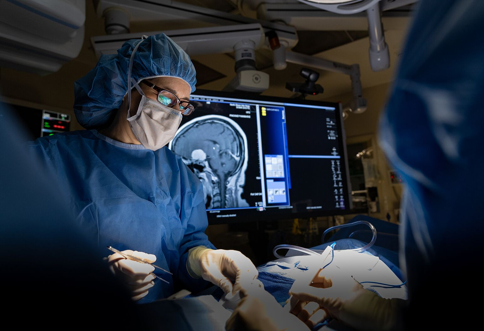 A surgeon wearing a mask and scrubs operates.