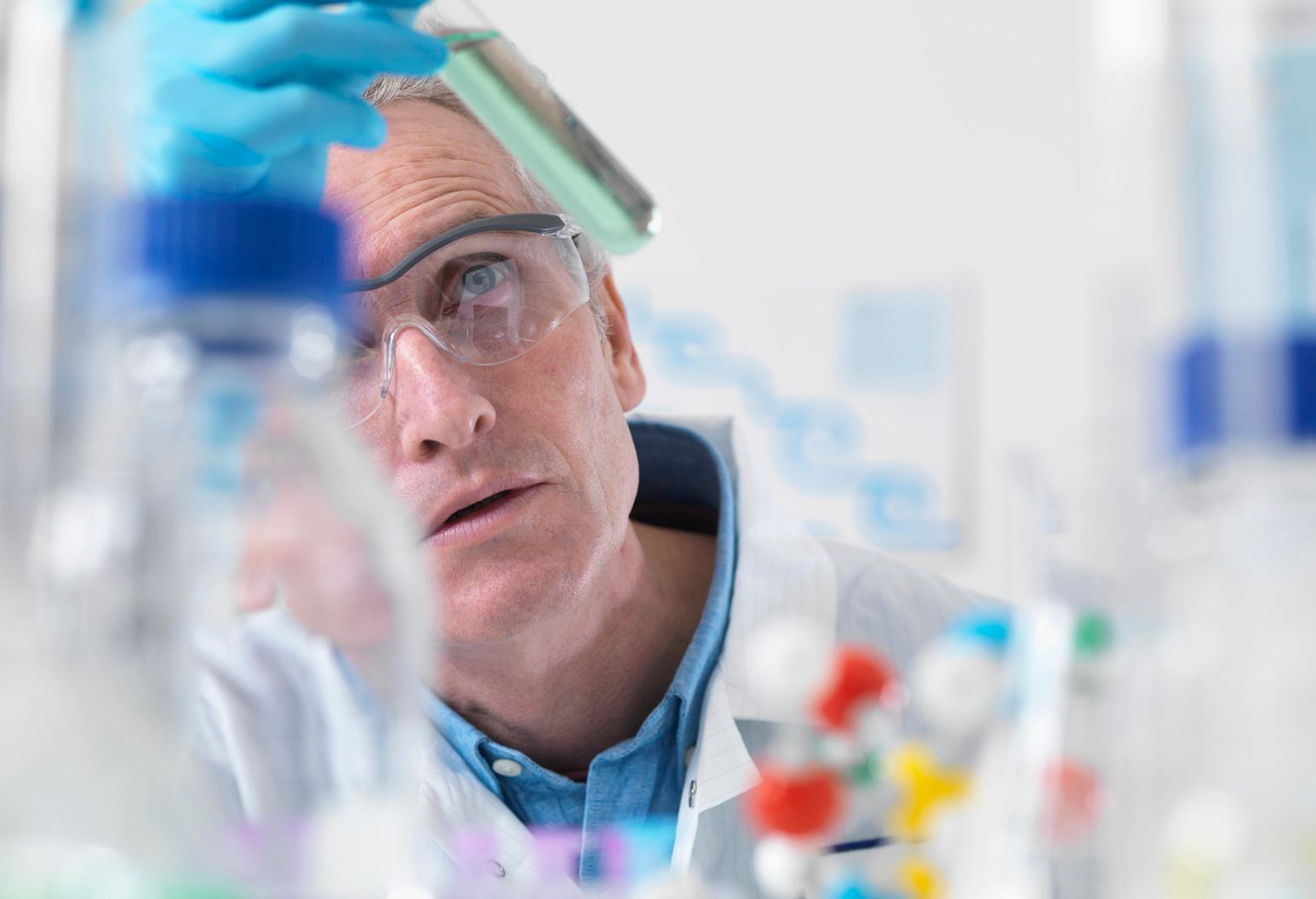 Man wearing lab coat, gloves and glasses examines a test tube with liquid in it.