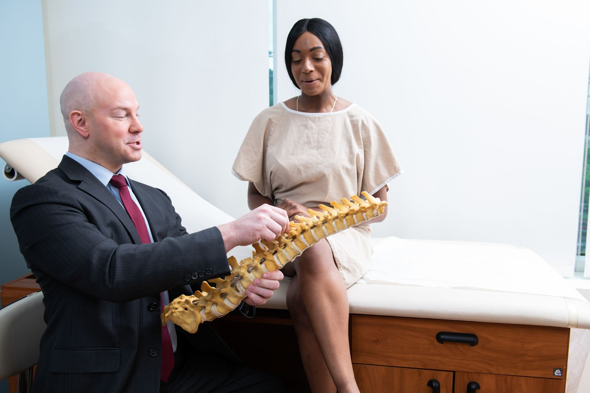 A doctor shows a female patient a model of the spine.