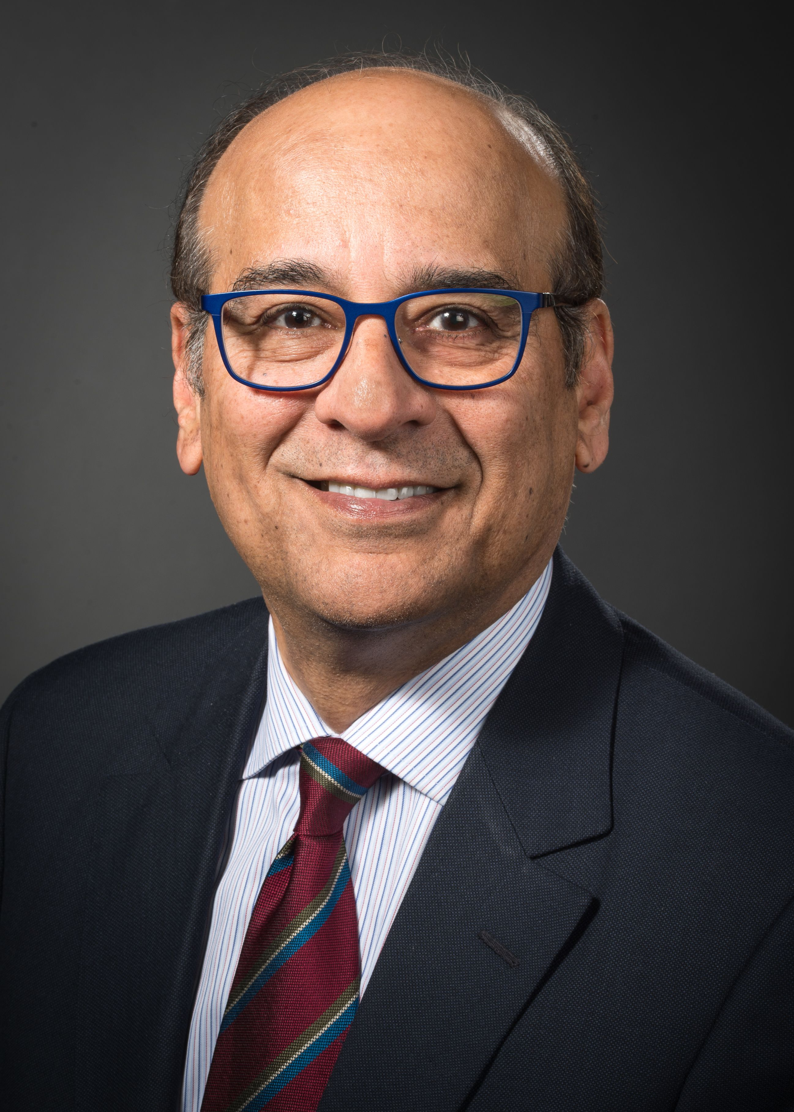 Raj Narayan, MD, head shot wearing a maroon tie with blue stripes and blue glasses