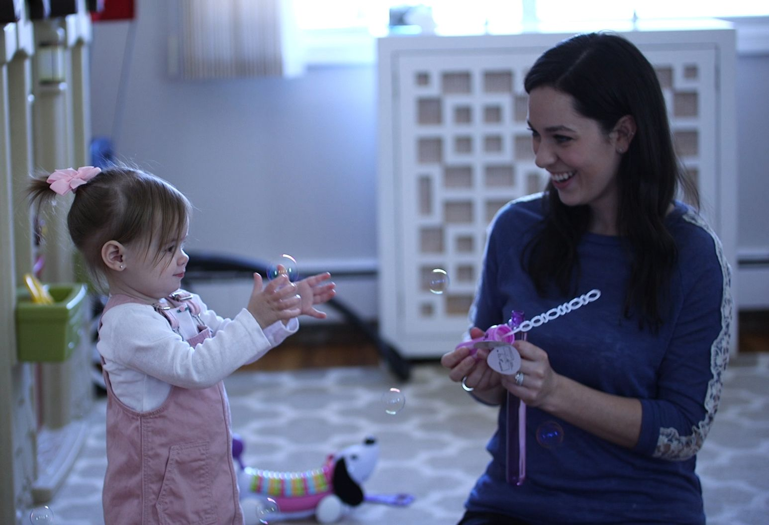 A toddler girl plays with bubbles next to her mom, who is smiling. The little girl is wearing pink overalls with a pink bow in her hair.
