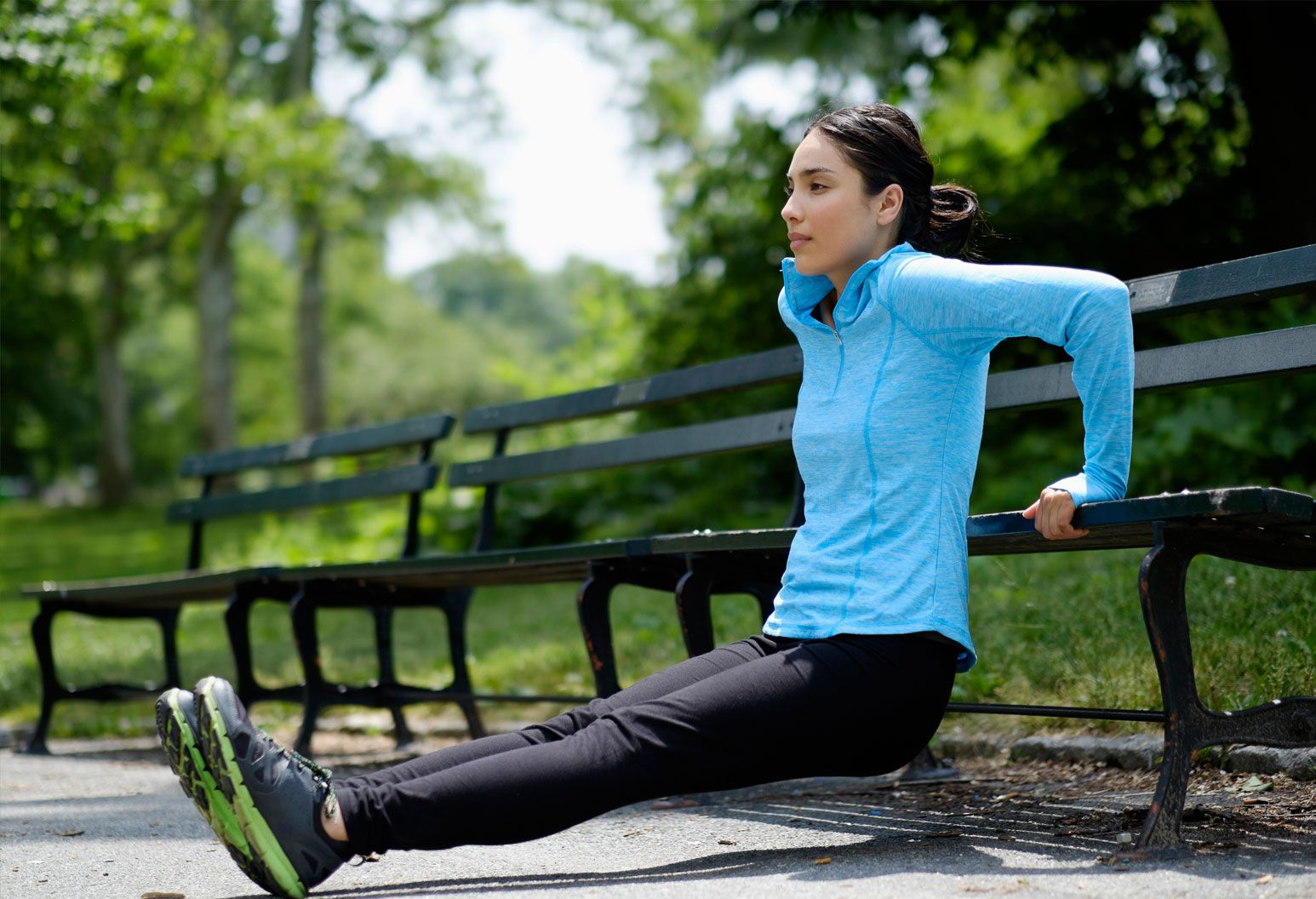 A young woman leans on a New York City park bench and stretches. She's wearing a bright blue athletic sweatshirt and black leggings and sneakers. Her dark hair is pulled back in a low bun.
