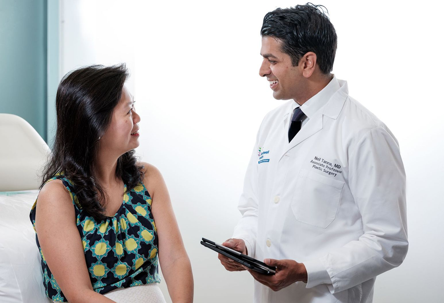 A male doctor with dark hair wears a white lab coat and holds an ipad as he speaks to a female patient who is sitting on an examination table. The woman is wearing a navy, turquise and yellow patterned shirt. They are both smiling.