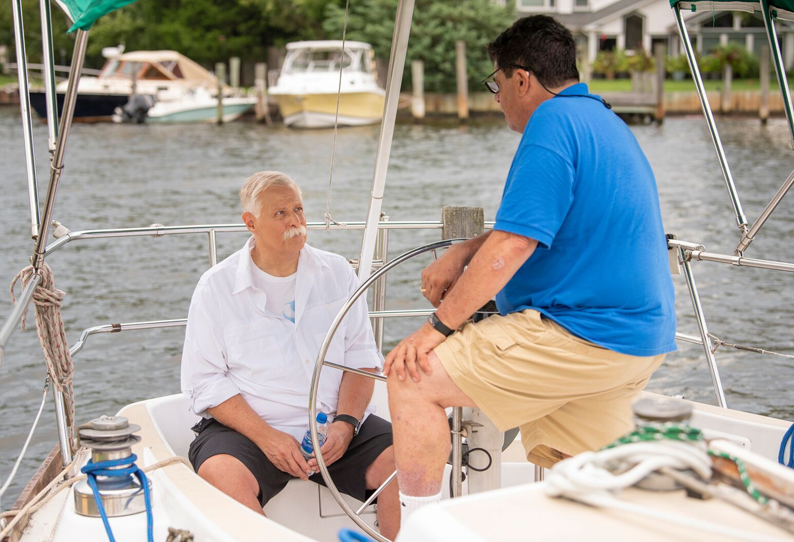 Two men enjoy an afternoon out on the water in a boat.