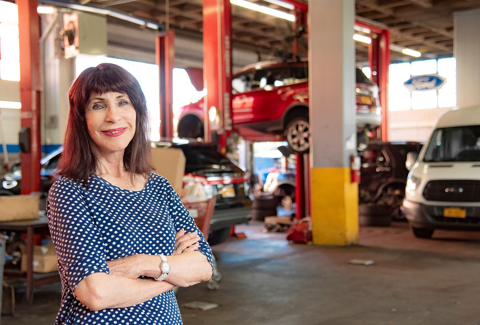 Woman with dark hair wearing a navy and white polka dot shirt in a car dealership.