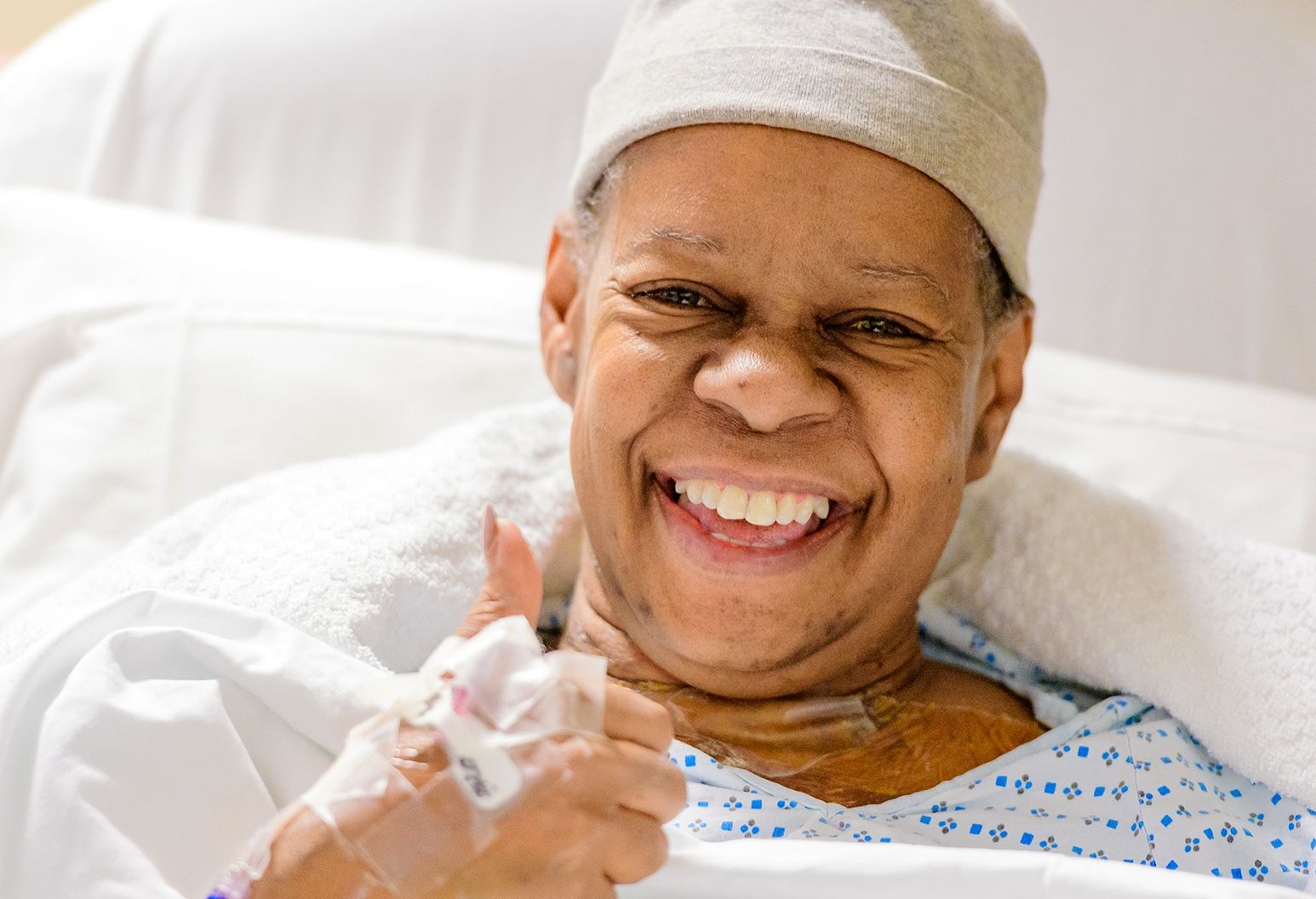 A female patient smiles and gives a thumbs up from a hospital bed after having a heart transplant.