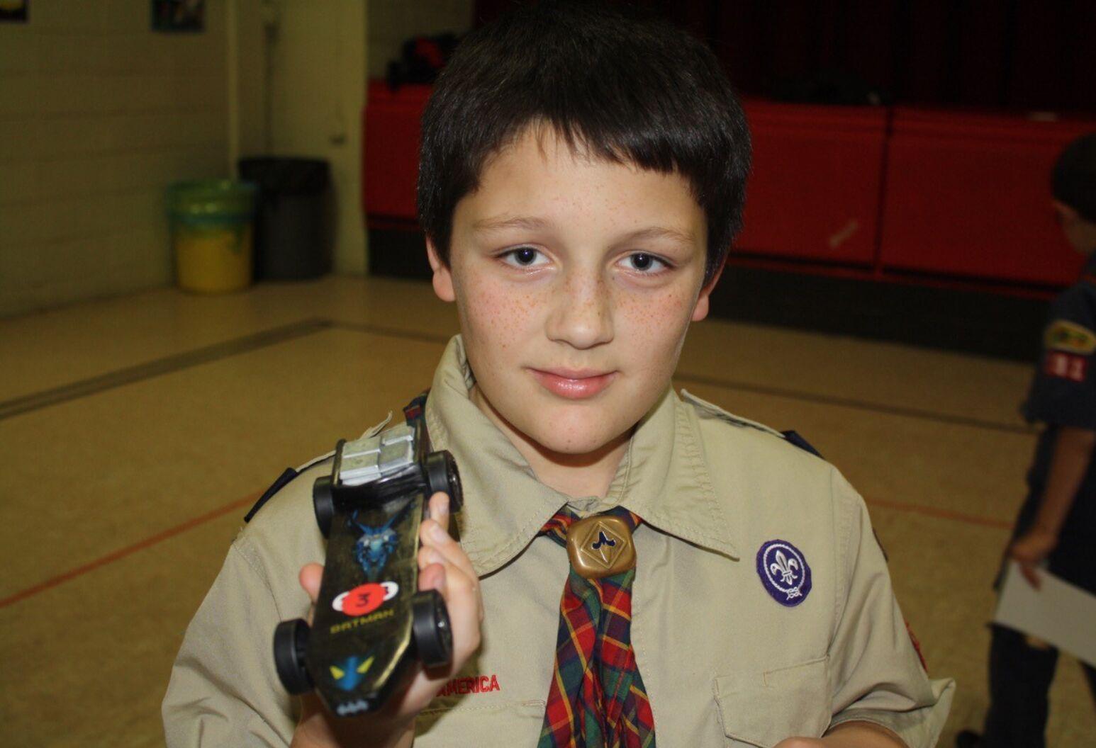 Boy scout holding a box car