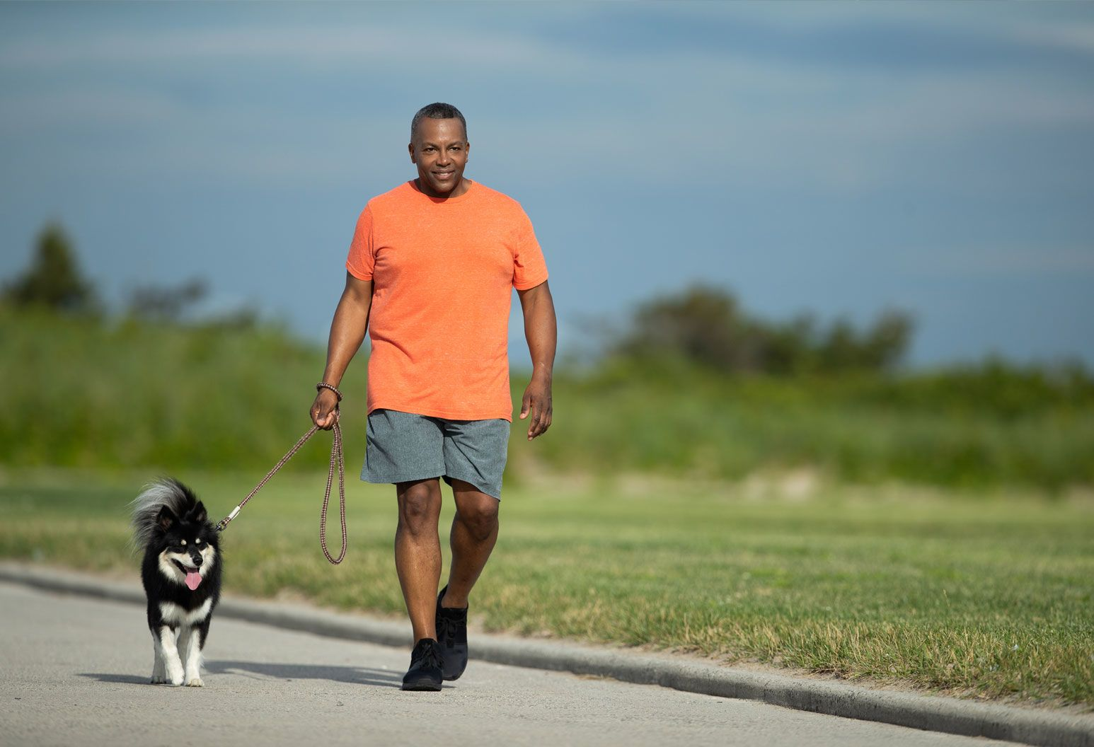 A middle aged male wearing an orange t-shirt walks with his dog at the beach.