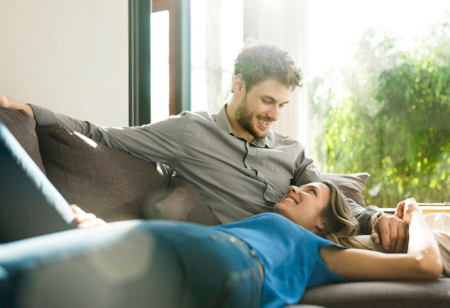 affectionate couple smiling at each other while relaxing on couch in modern design living room with large garden windows