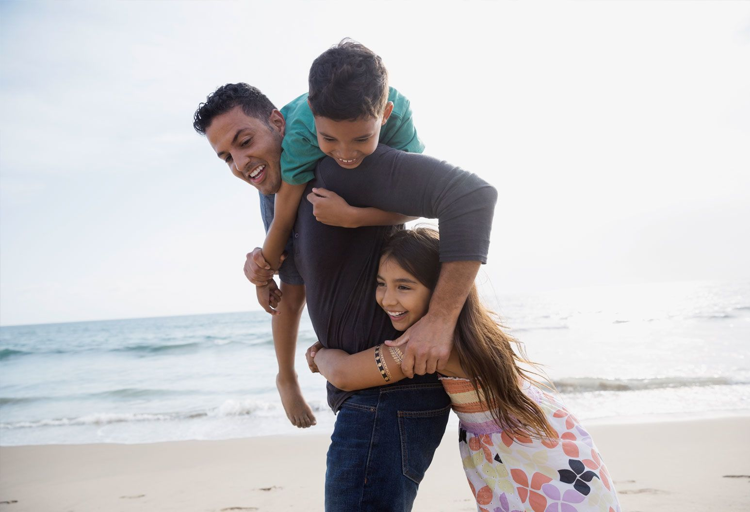 A father and his two children, a boy and girl, play together on the beach. The boy is on the dad's back and the girl has her arms wrapped around his waist.