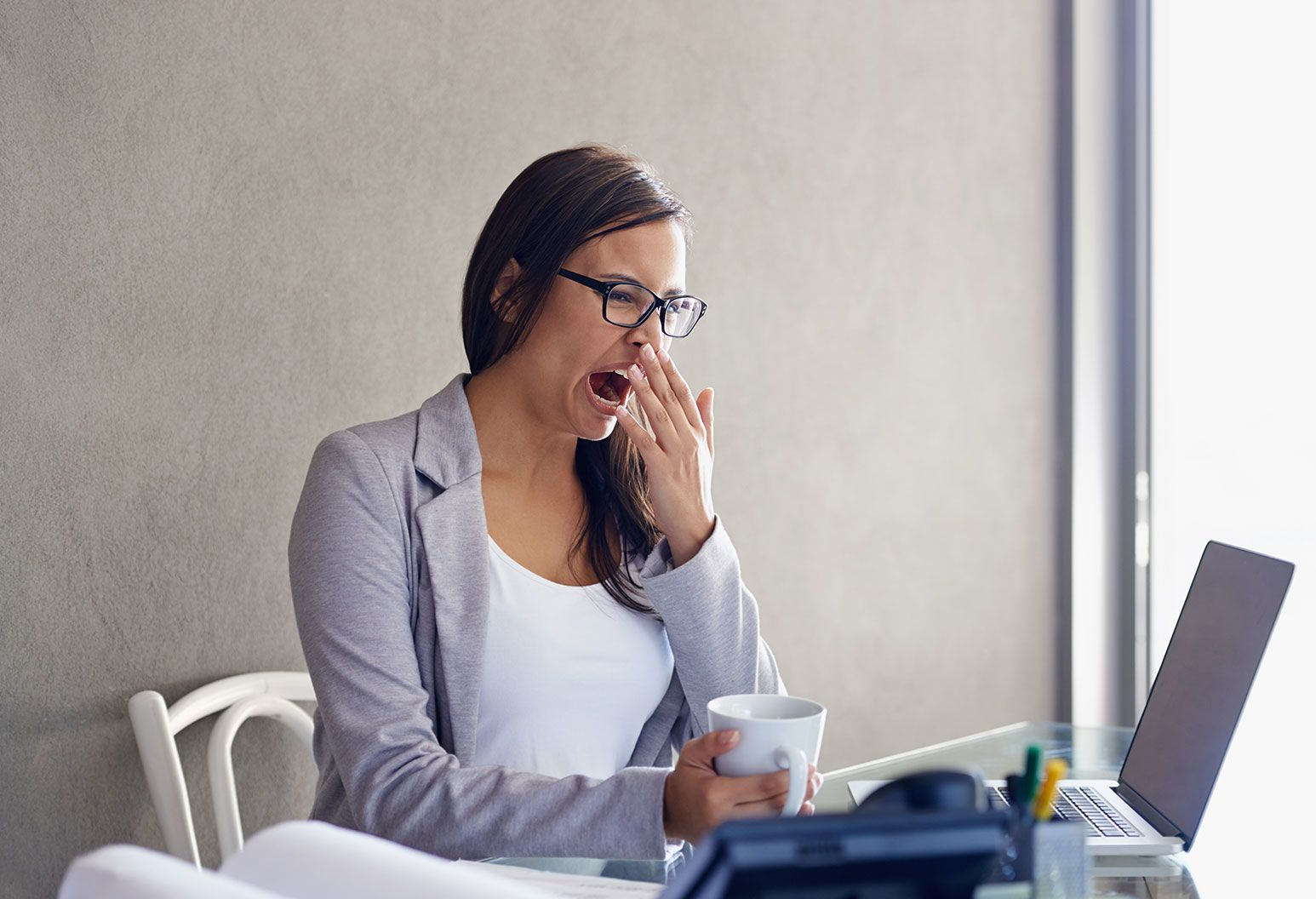 Thyroids causing exhaustion and weight gain: A woman in glasses wearing a grey blazer over her white blouse yawns as she sits at a desk. She is covering her mouth with one hand while holding a ceramic white cup in the other. On the desk is an open laptop.