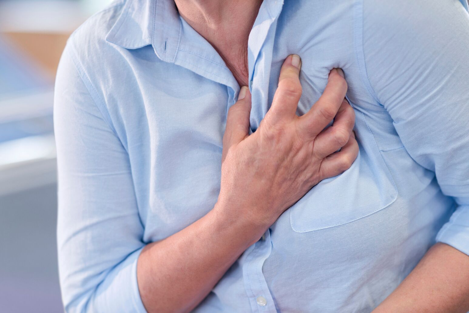 A woman holds her chest during a heart attack