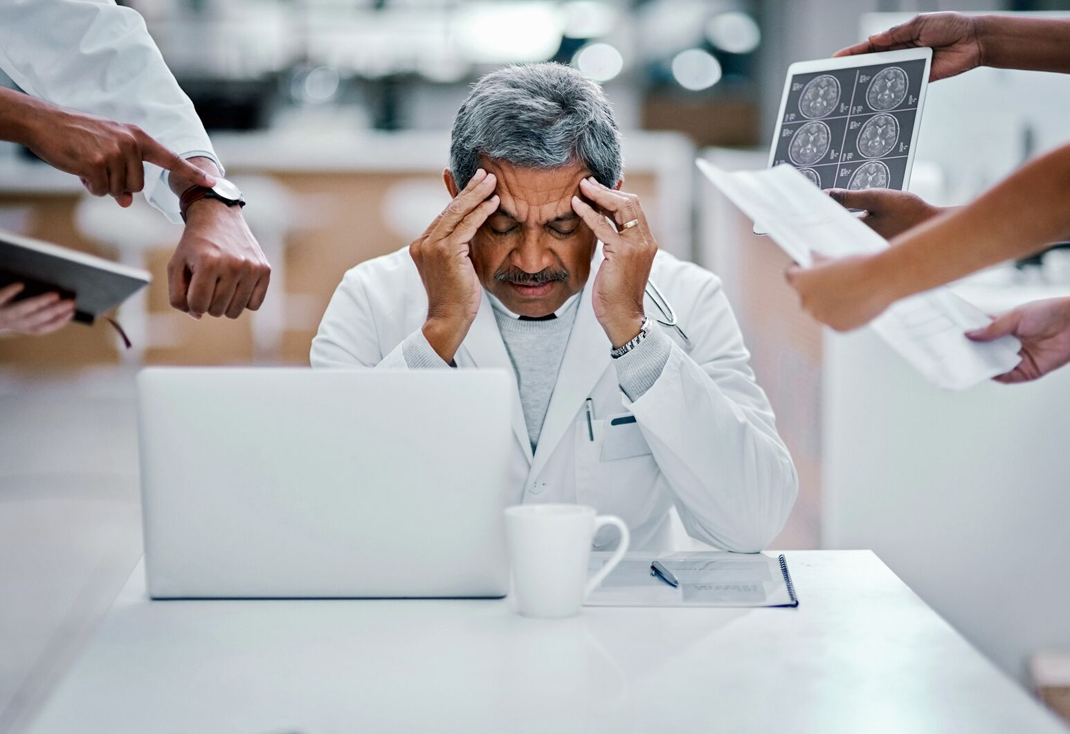 Surrounded by stressors, a physician holds his head