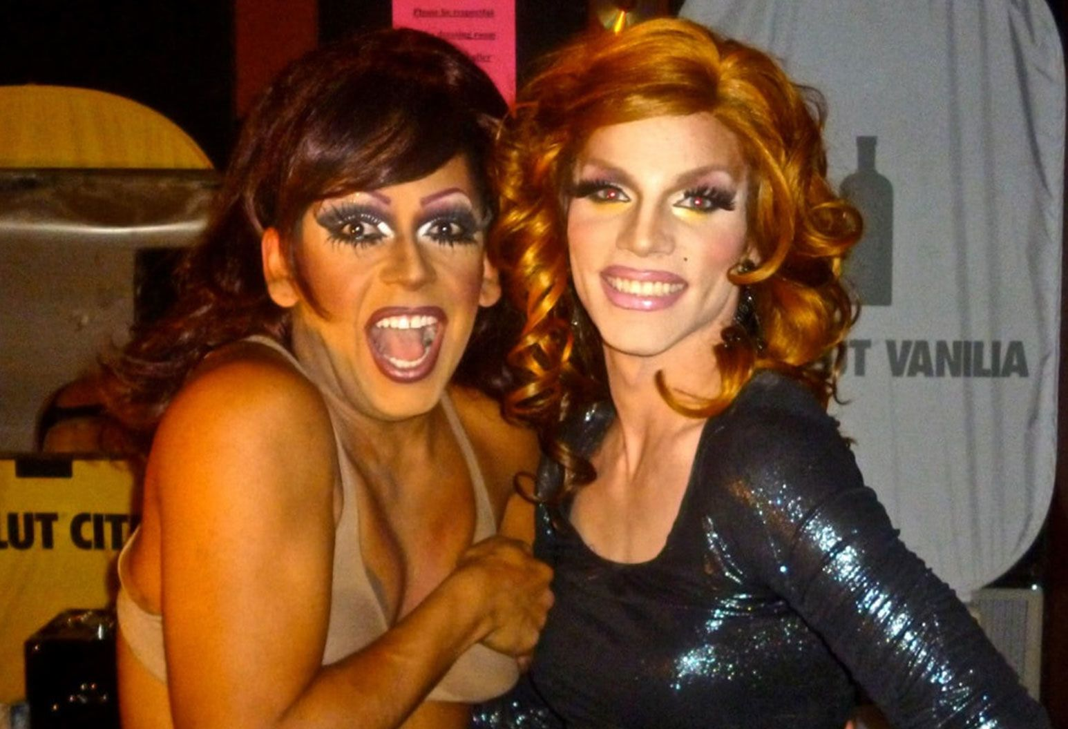 Two men in drag stand next to each other and smile for the camera. One is in a bra with a brunette wig, the other is in a black dress with a red wig.