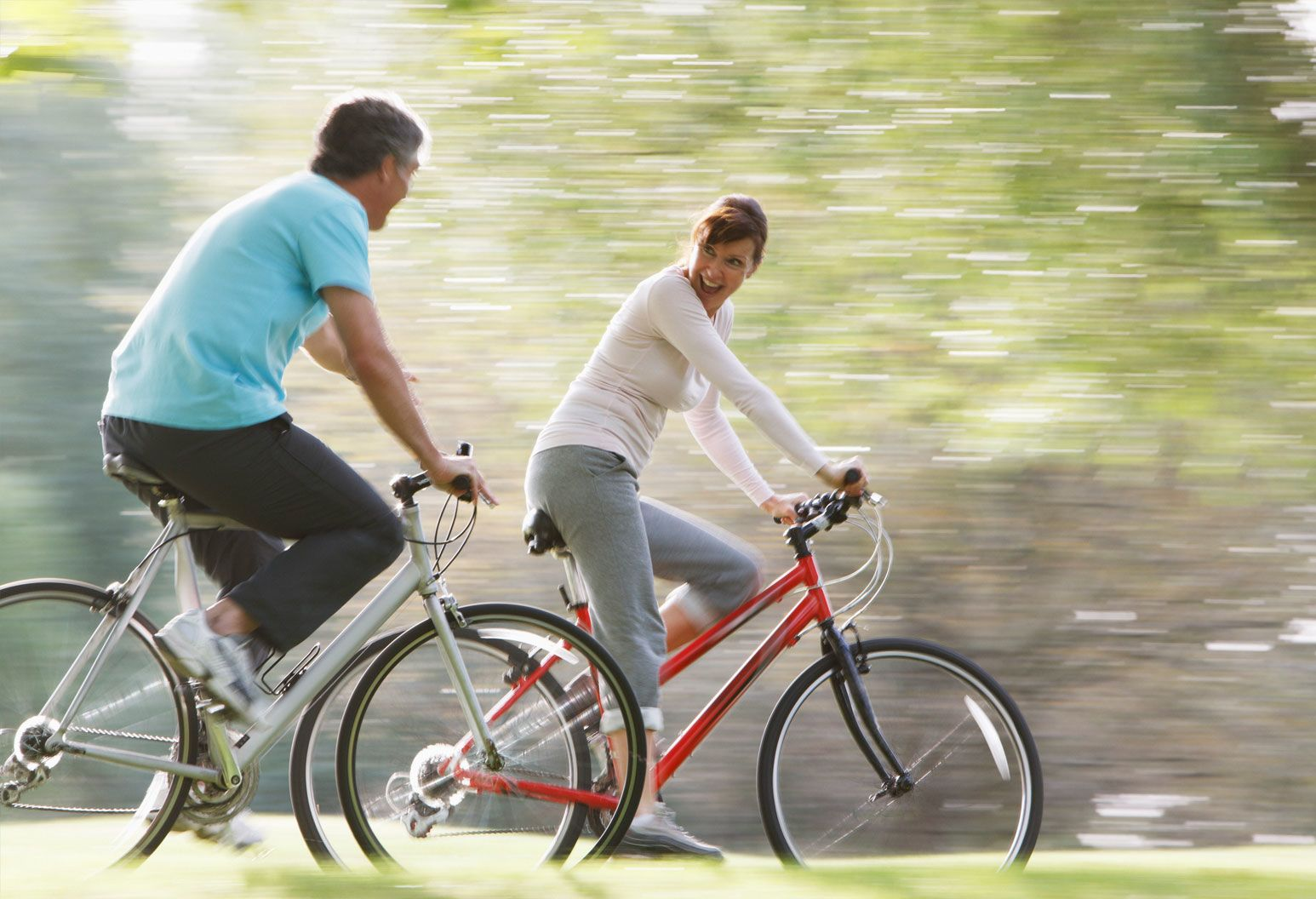 A middle-aged couple bikes together in a park. The woman is in front and looks back, playfully smiling at the man.