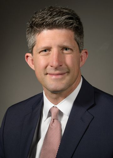 Joseph Schulman wearing a dark suit and red and white stripped tie