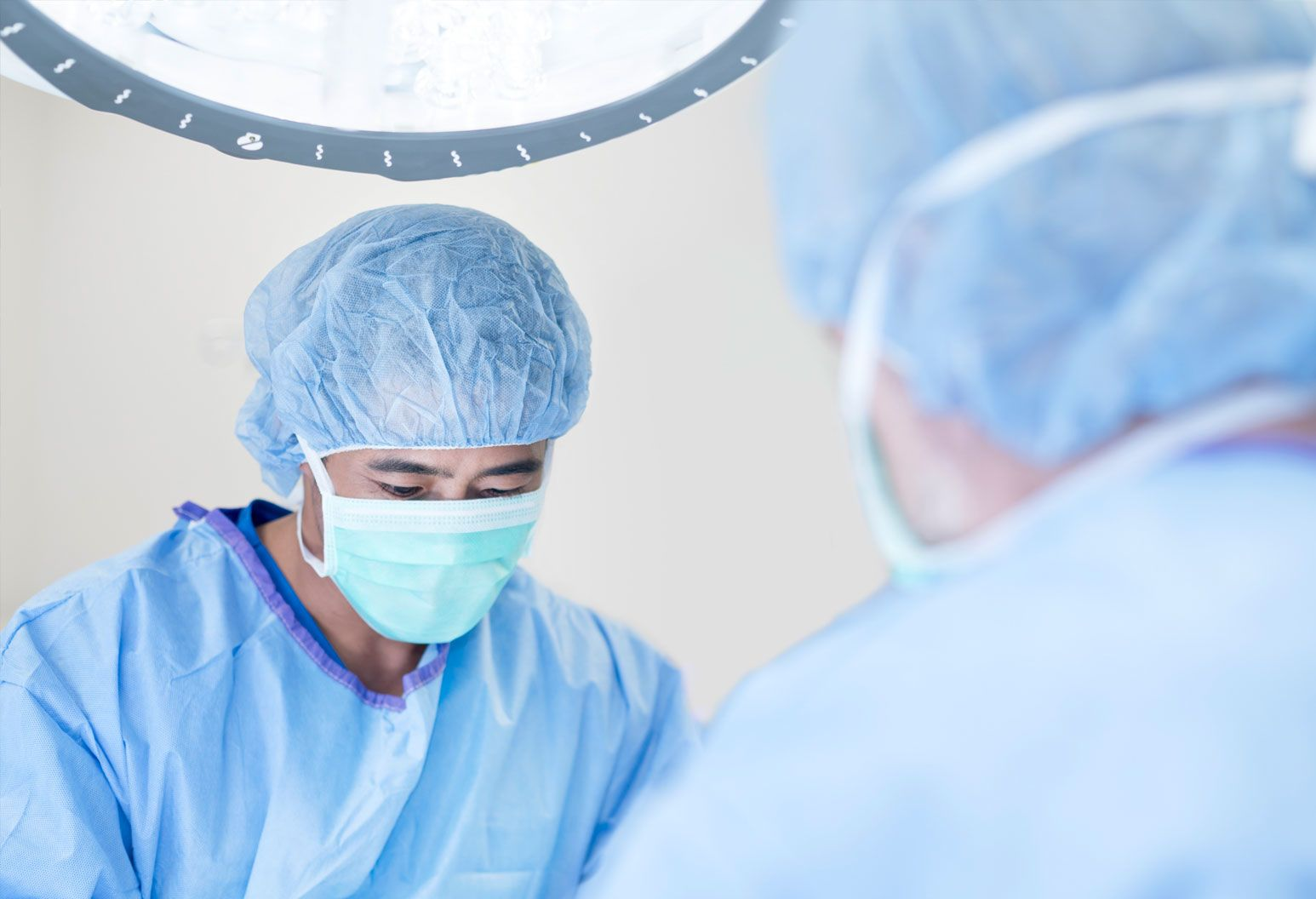 Close up of male surgeon wearing blue scrubs, hat and face mask in the operating room.