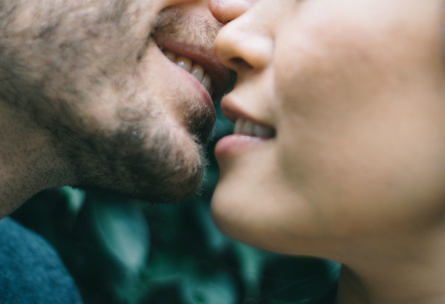 A man with a patchy, scruffy, beard is smiling as he brings his face close to a woman's lips, that also reveal a smile.