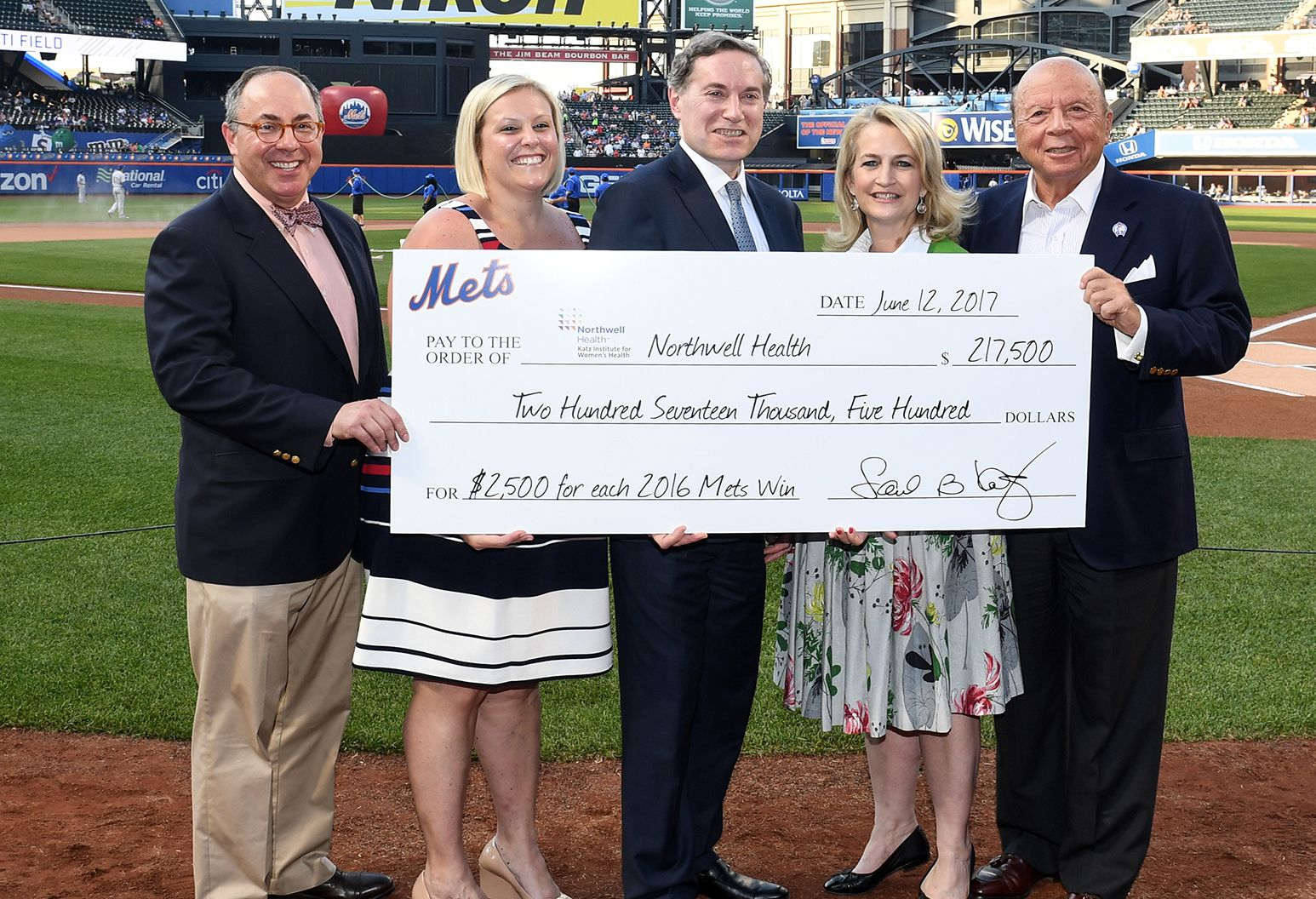 Dr. Andrew Menzin, Victoria Faustini,  Dr. Lyle Leipziger and Dr. Stacey E. Rosen receiving a check from Saul Katz at Citi Field, home of the New York Mets.