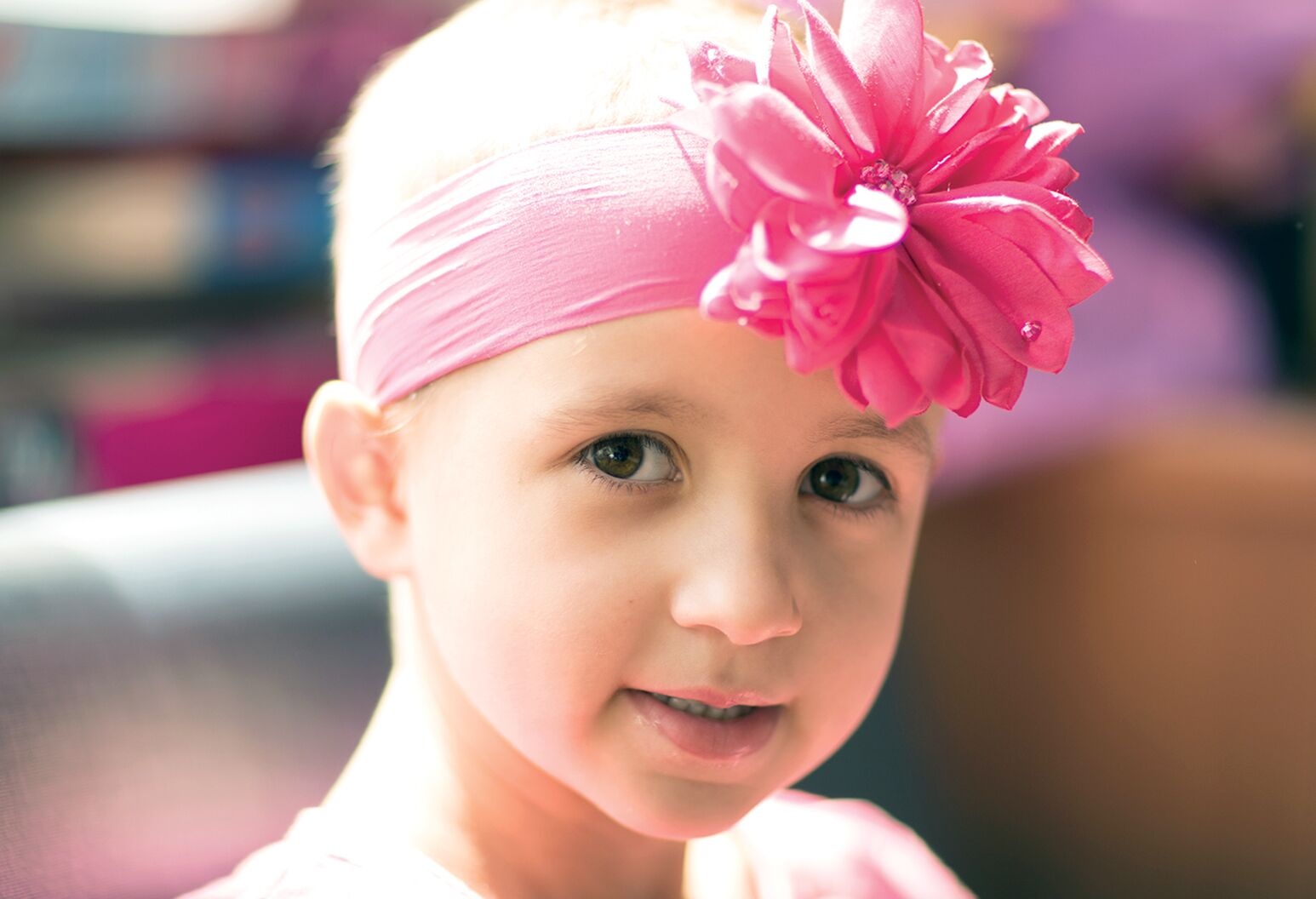 Young girl wearing a pink headband with a flower.