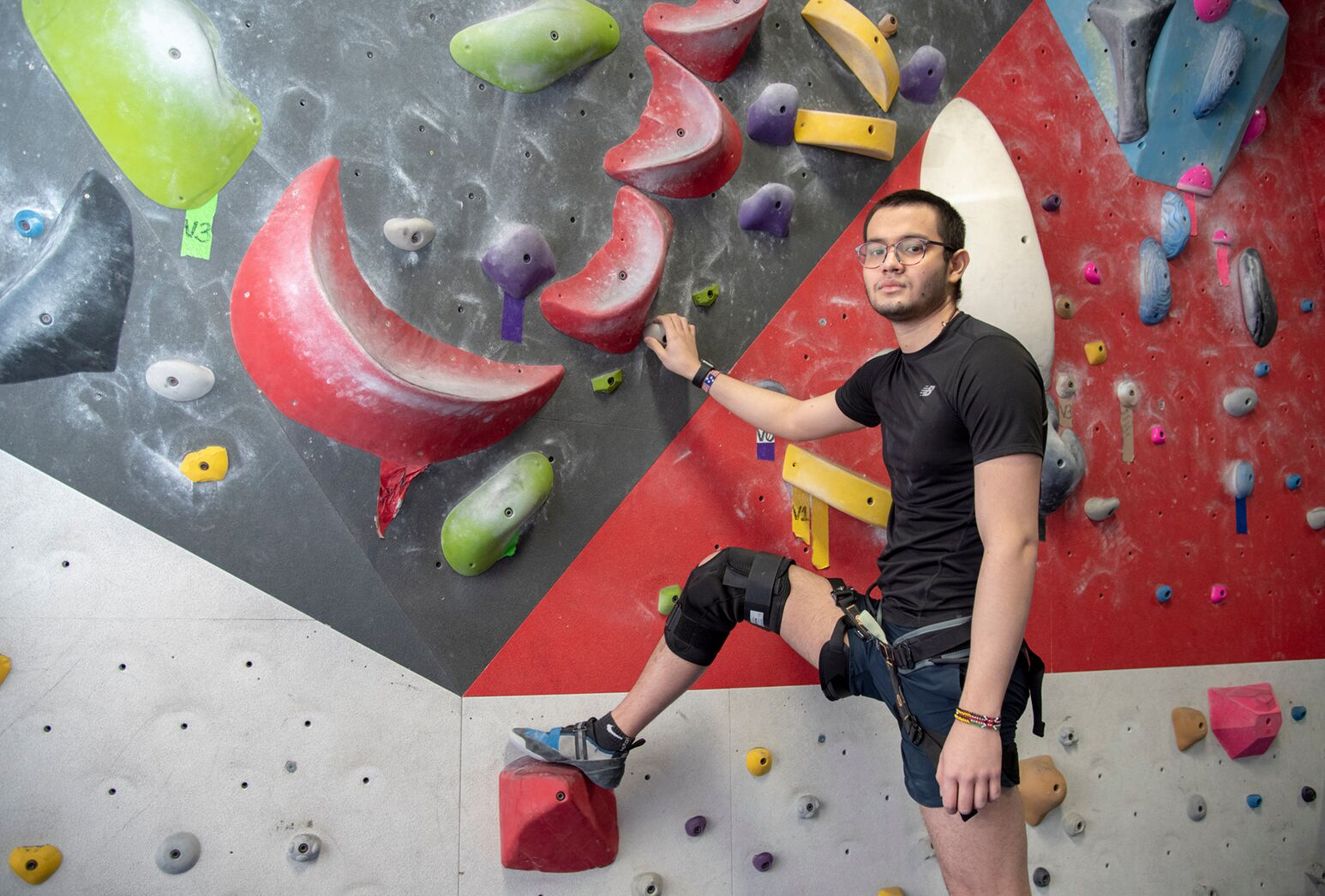 Young man in front of colorful climbing wall