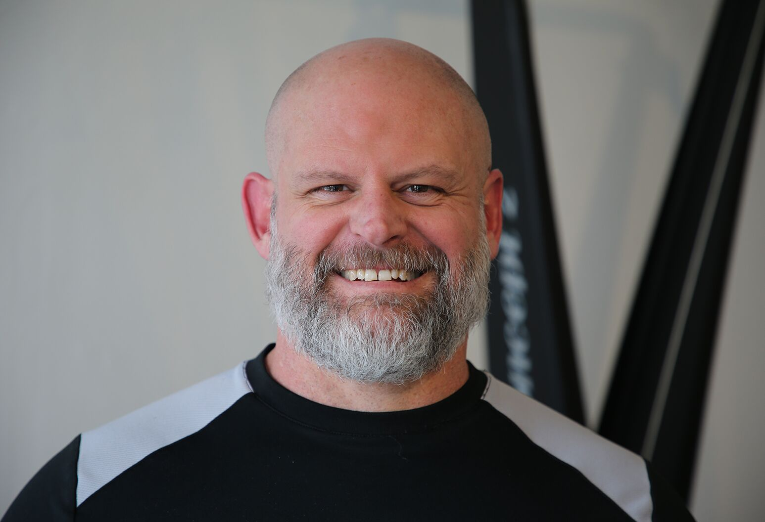 Smiling man in his 40s standing in front of gym equipment.