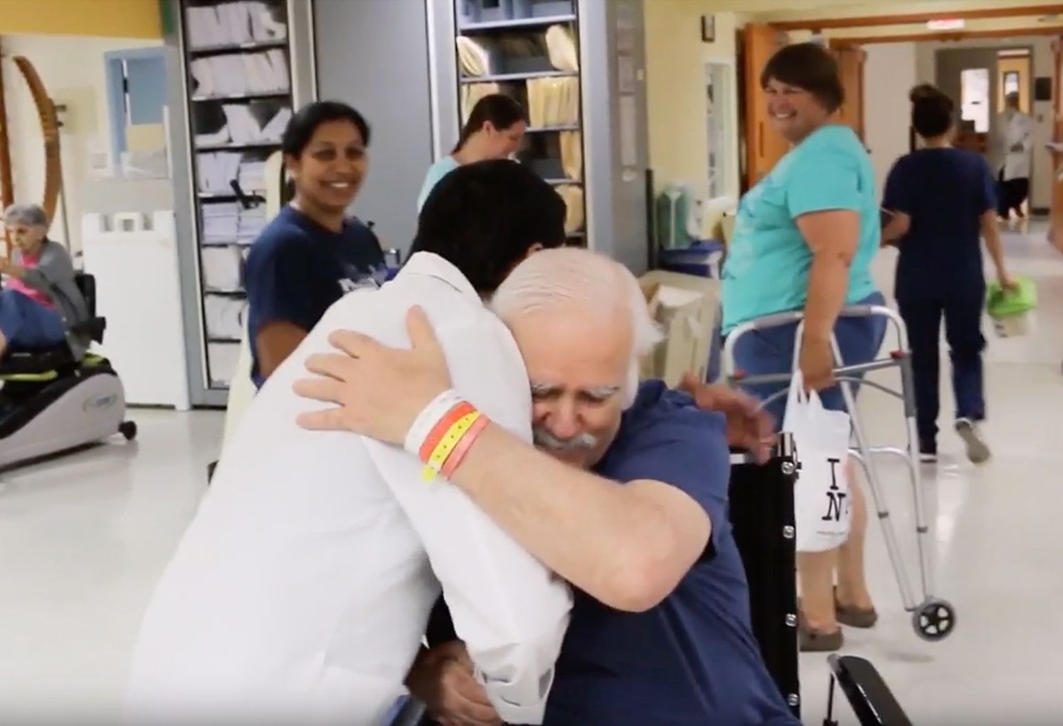 Male in white lab coat hugs older man with gray hair and blue shirt in wheelchair