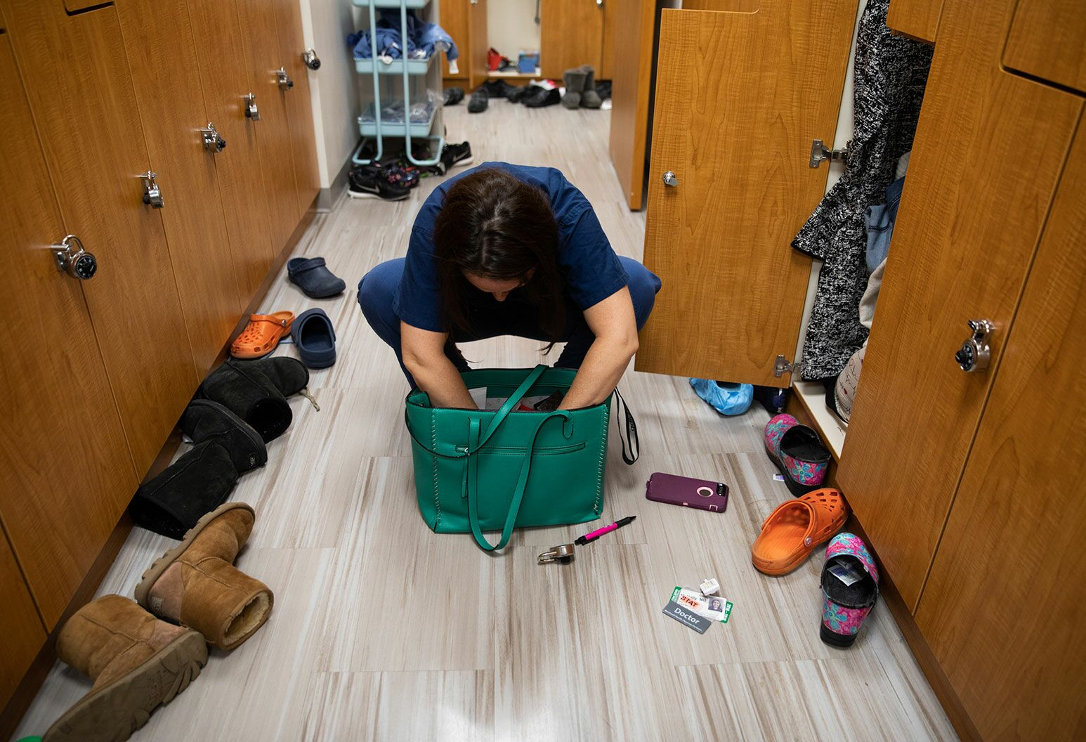 A woman in blue scrubs crouches over a teal bag in a messy locker room searching for something.