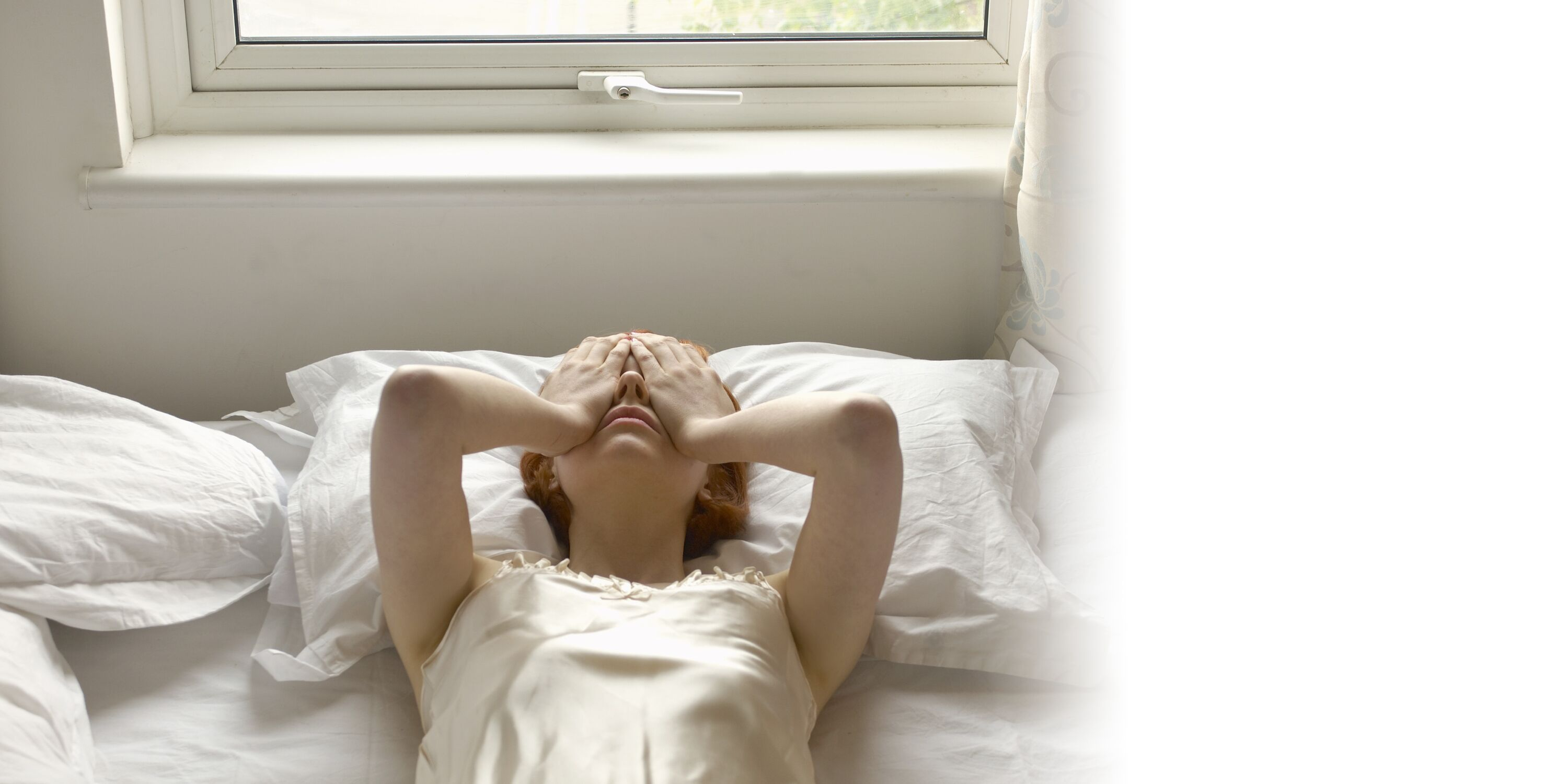 A woman lays in bed with her hands covering her face.
