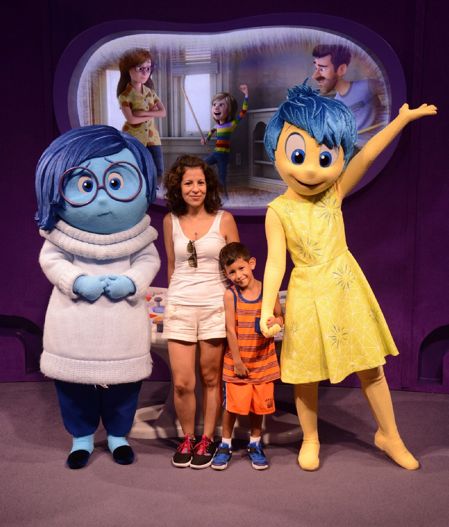 Mother and son on vacation pose with theme park characters