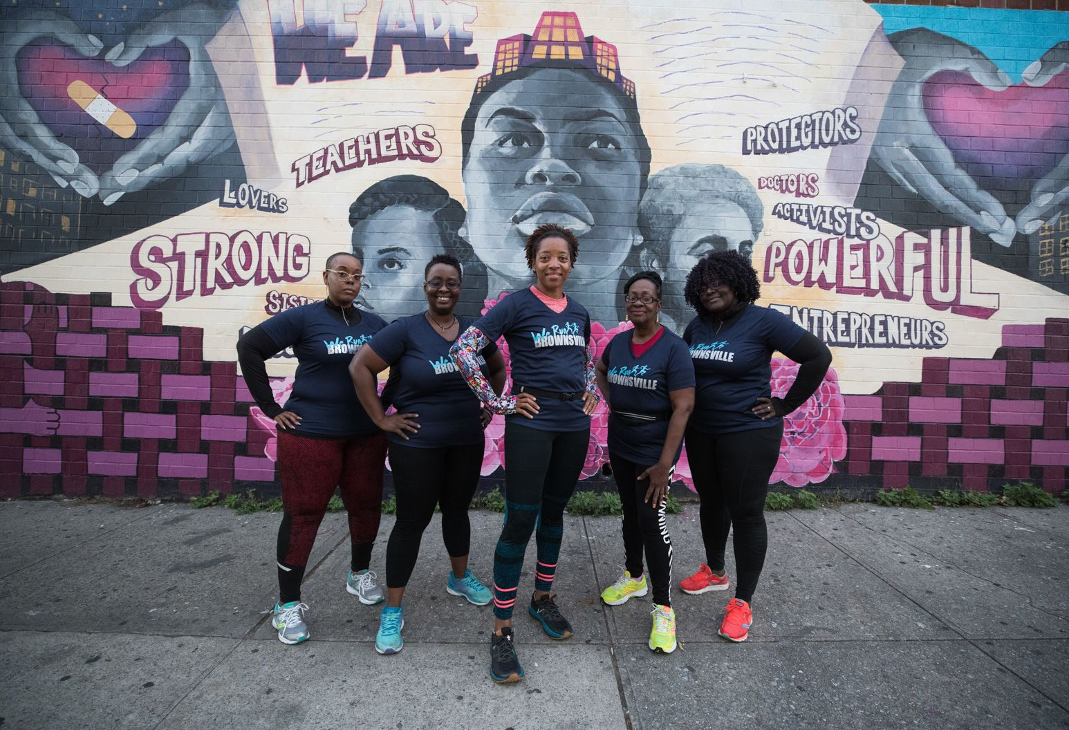 Five African American women stand with hands on hips wearing matching blue t-shirts, leggings and running sneakers. They pose in front of a mural that has a face and many words on it.
