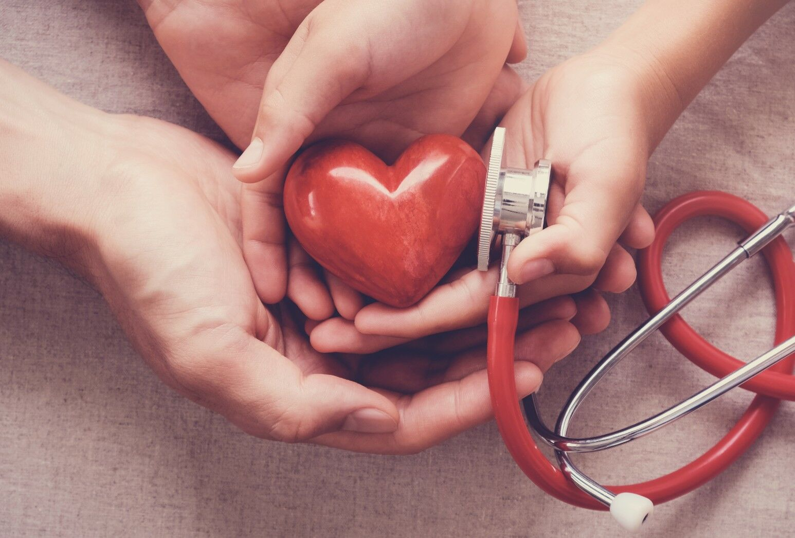 Three sets of different sized hands tenderly hold a wooden heart and a stethoscope.