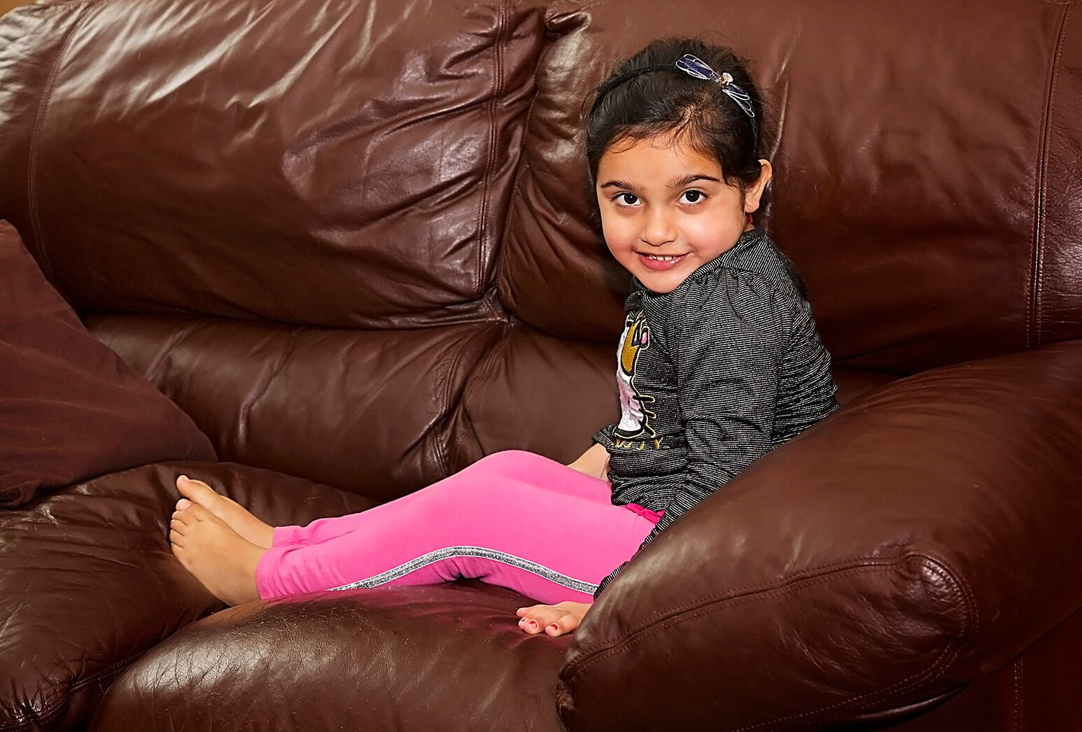 Young girl relaxes on the couch in her home.