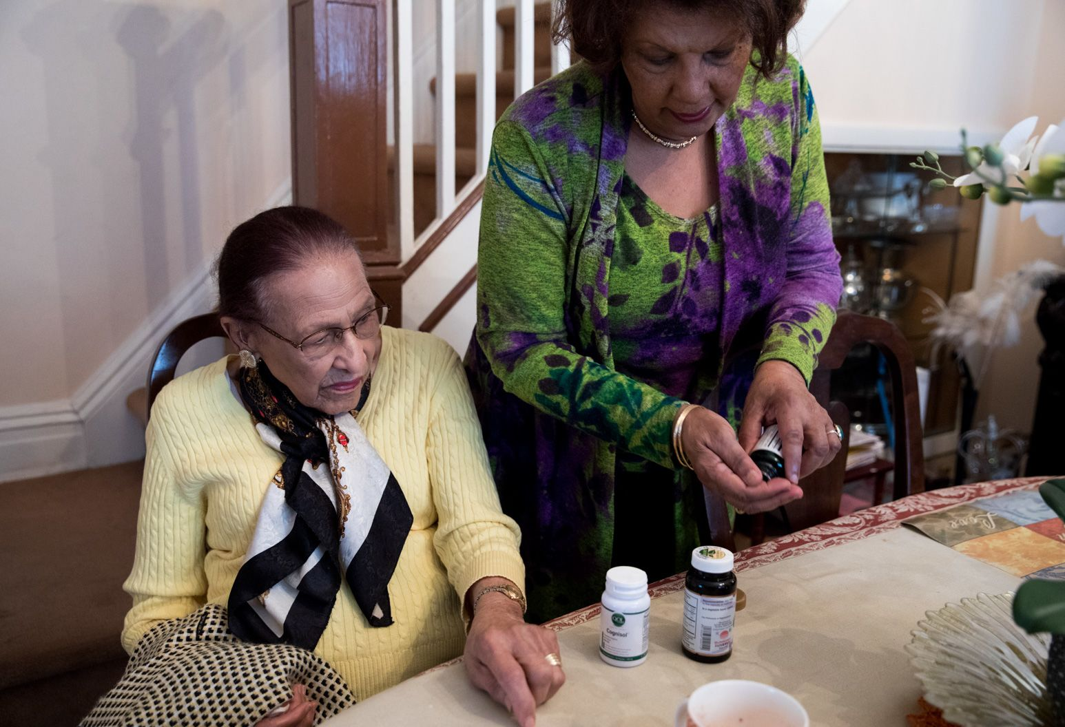 Woman prepares medication for an older woman at the dining table.