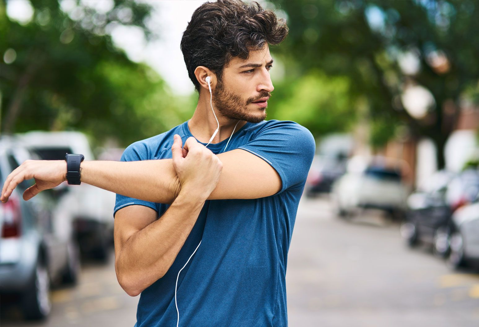 A man in his 20s stretches his arm outside. He wears headphones and a t-shirt and looks like he's about to go for a run.