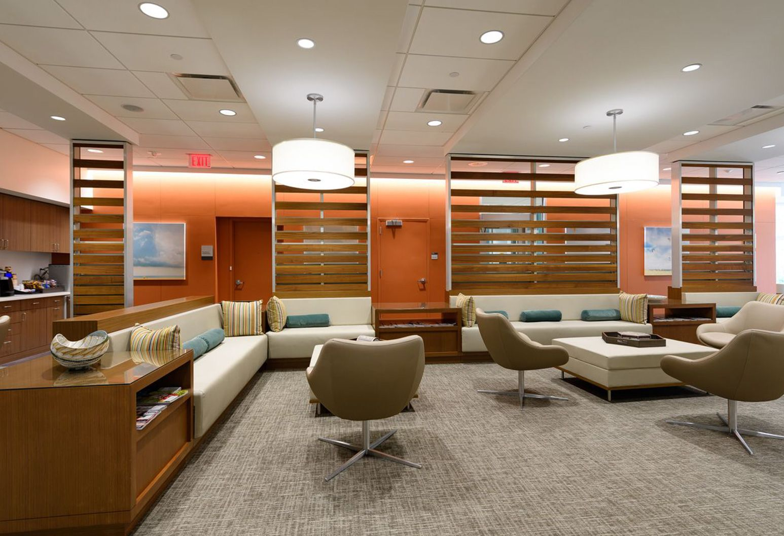 Modern waiting room with white couches,chairs, dark wood tables and accent wood paneling on dark orange colored walls