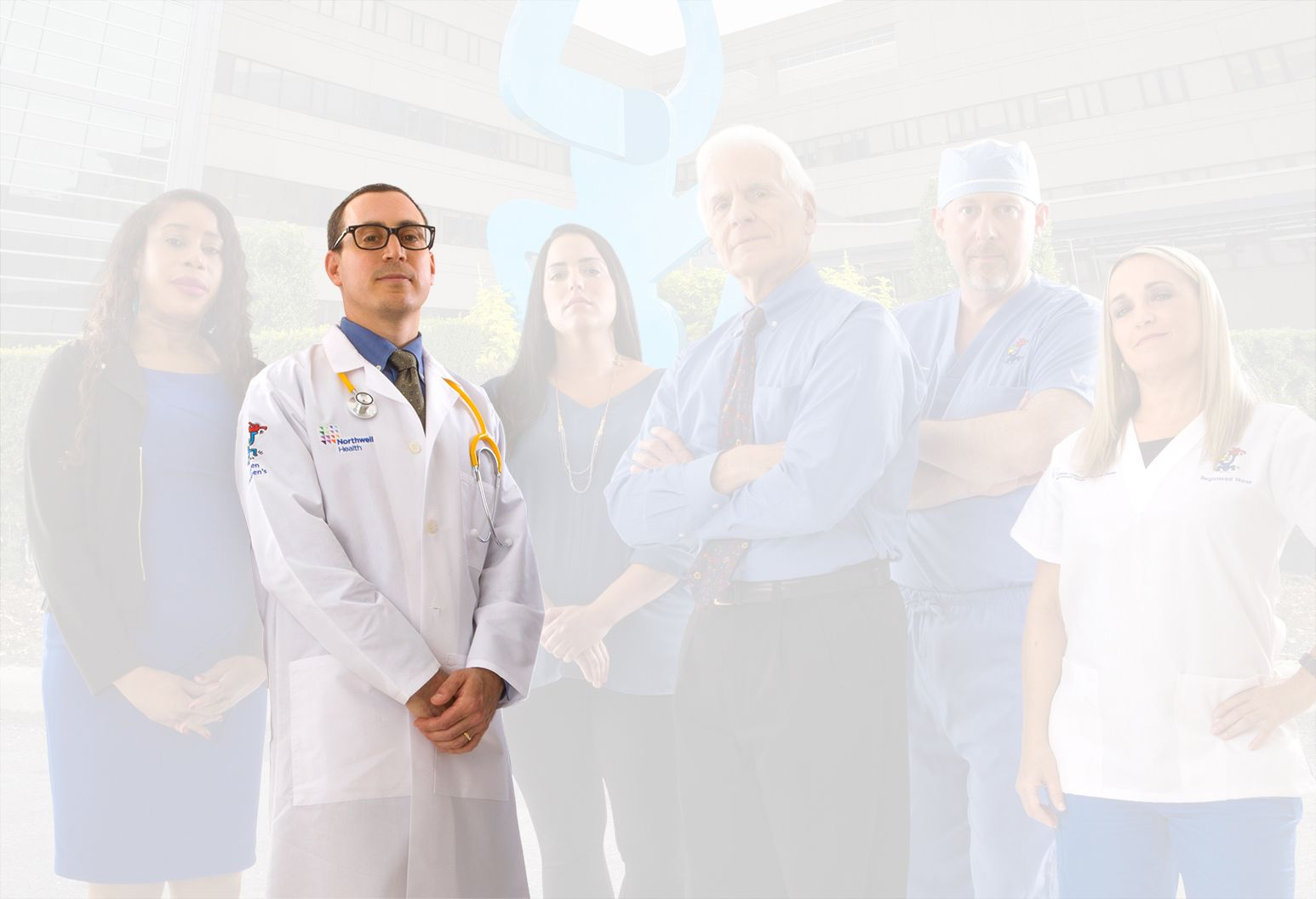 A doctor wearing a white lab coat with a Northwell Health logo separates from the rest of the team and the background.