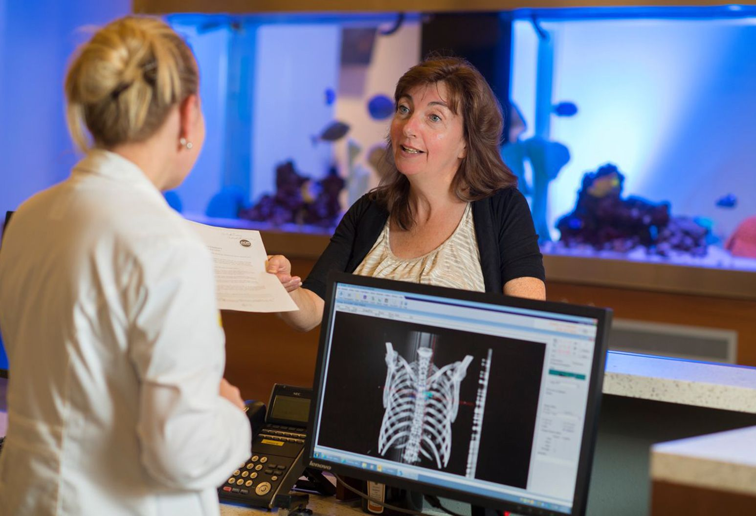 Female patient standing in front of a large fish tank hands paperwork to doctor wearing a white lab coat who is standing behind a reception desk. The computer monitor at the reception desk is displaying an image of the human skeleton