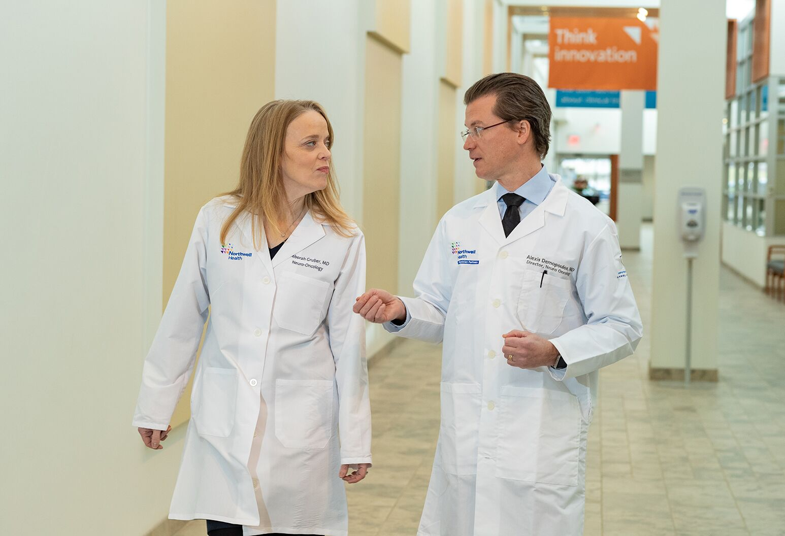 A female and male doctors walking down a hospital corridor.