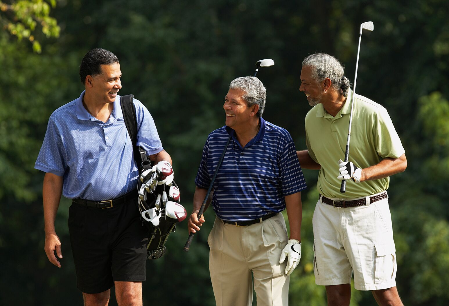 Three men smiling on a golf course