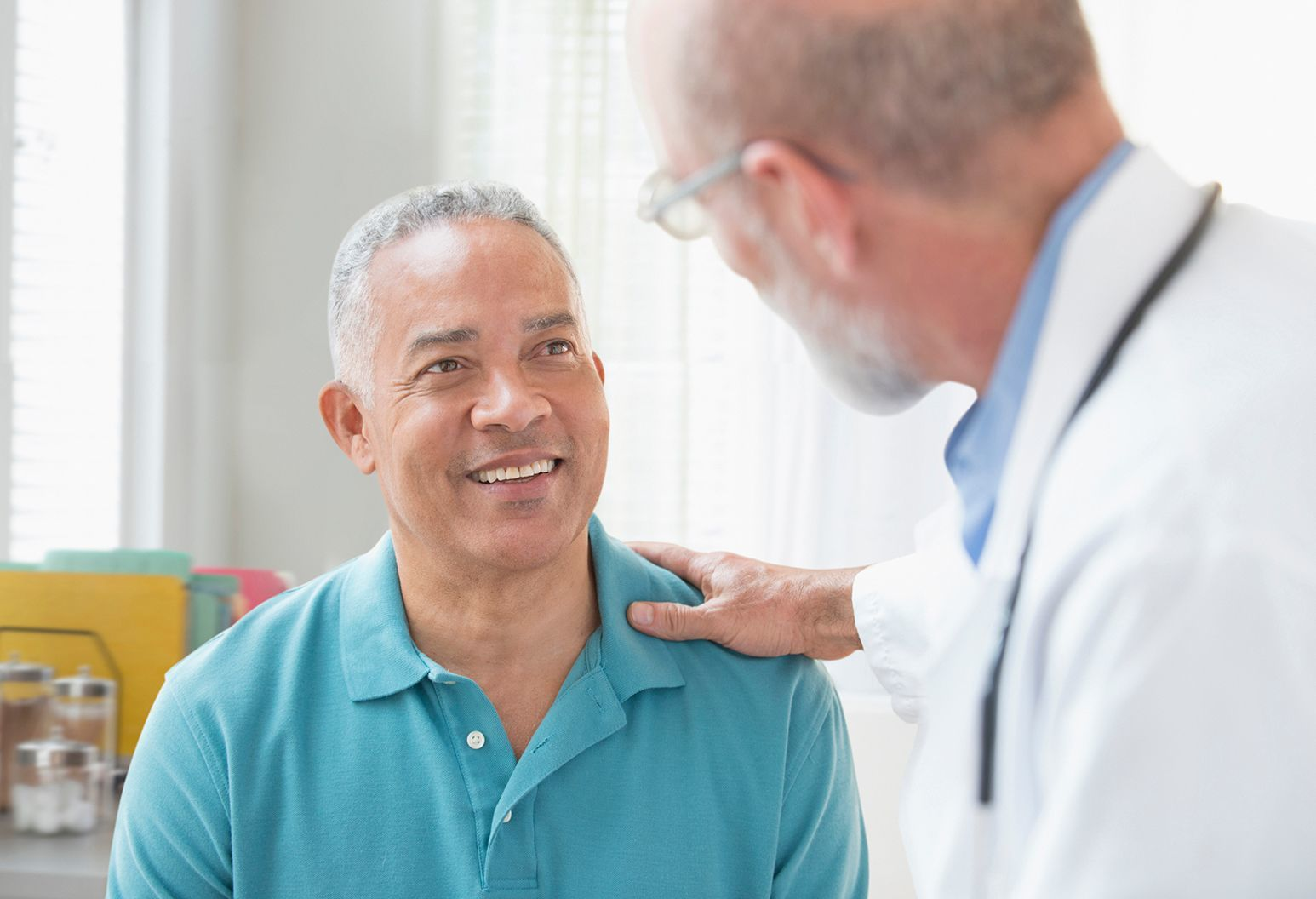 Man smiling while doctor has and on his left shoulder