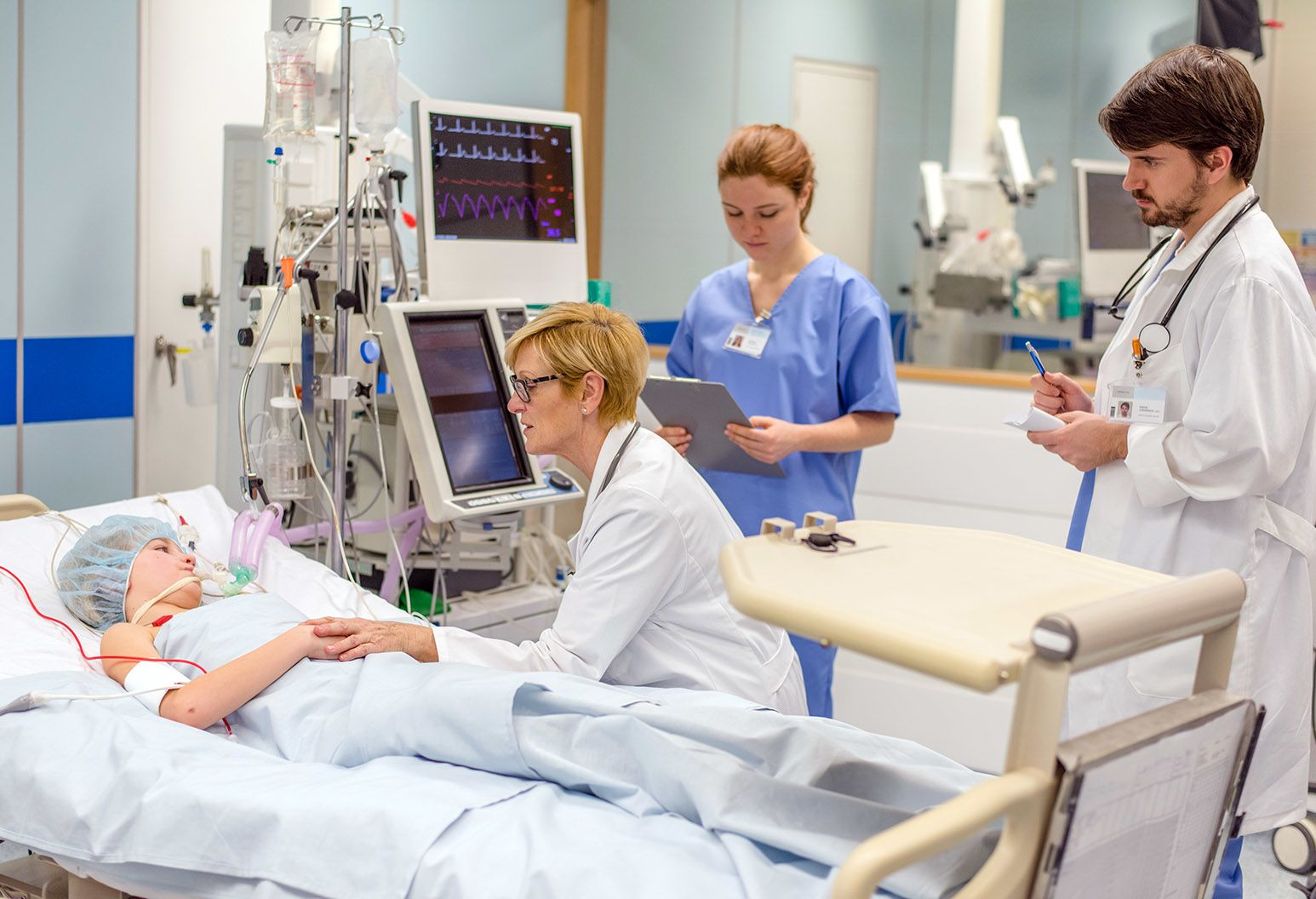 Clinicians with a boy in a hospital bed