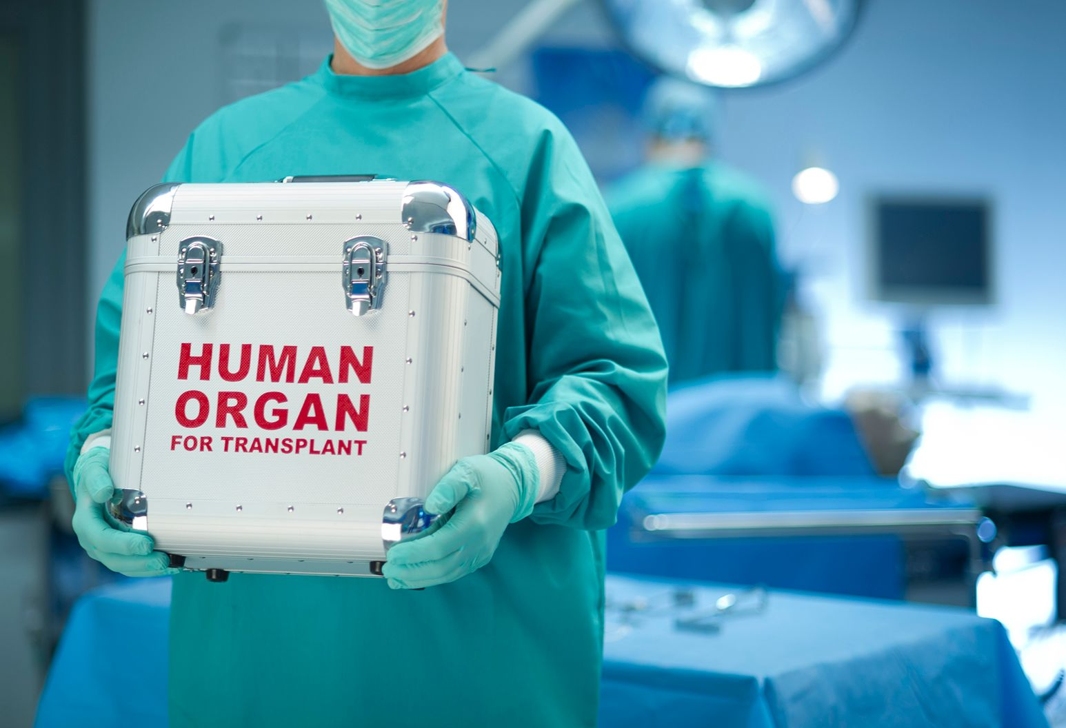 A person dressed in green surgical scrubs and wearing a green facemask and green rubber gloves is standing in an operating room and holds a grey metal box that has the words Human Organ for Transplant written on the front.