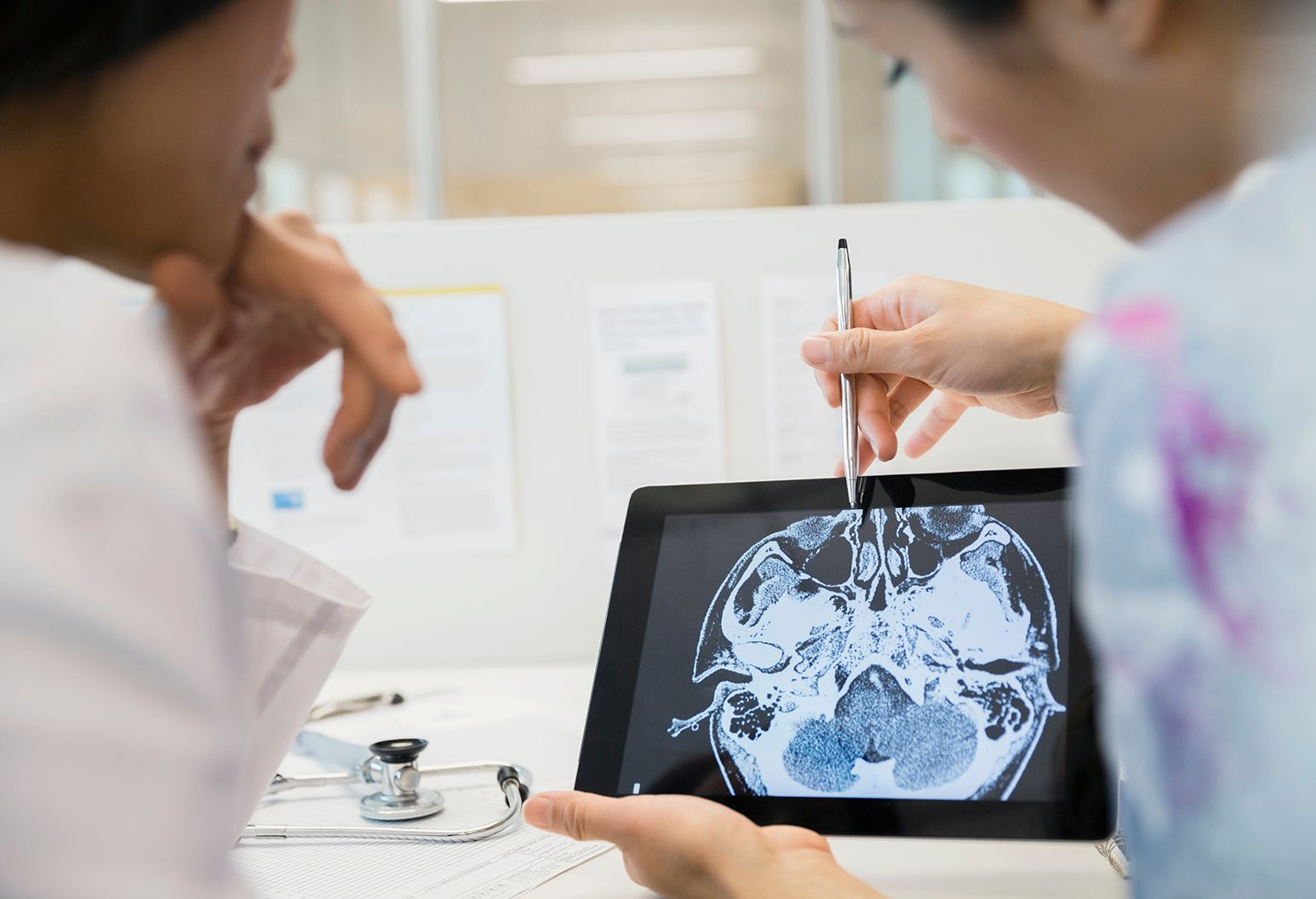 Two imaging technicians observing a brain scan on a tablet.
