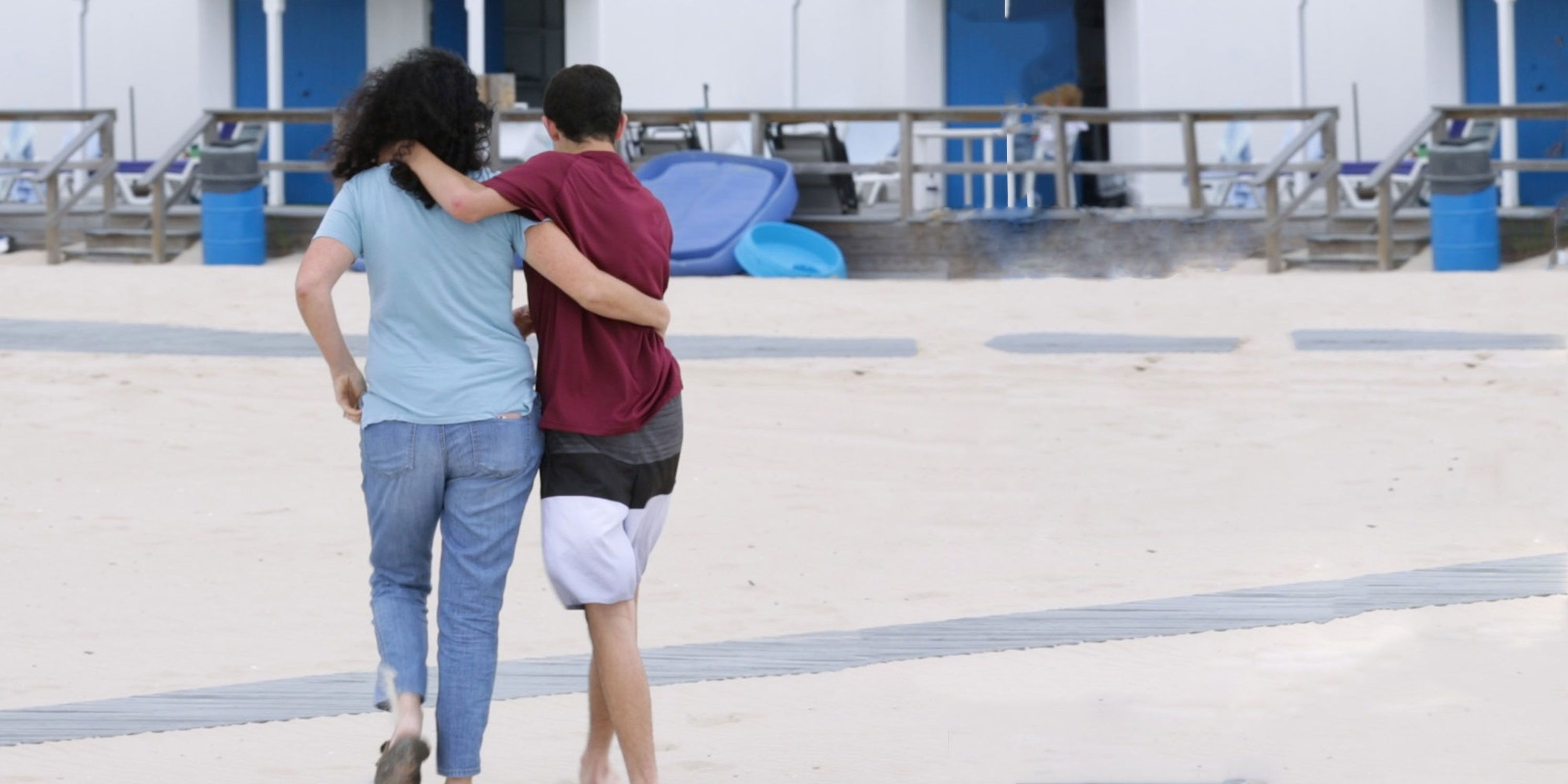 A woman wearing a blue shirt and jeans walks away from the camera with her arm around a young male teen wearing a red shirt and black & white shorts. His arm is around her shoulder.