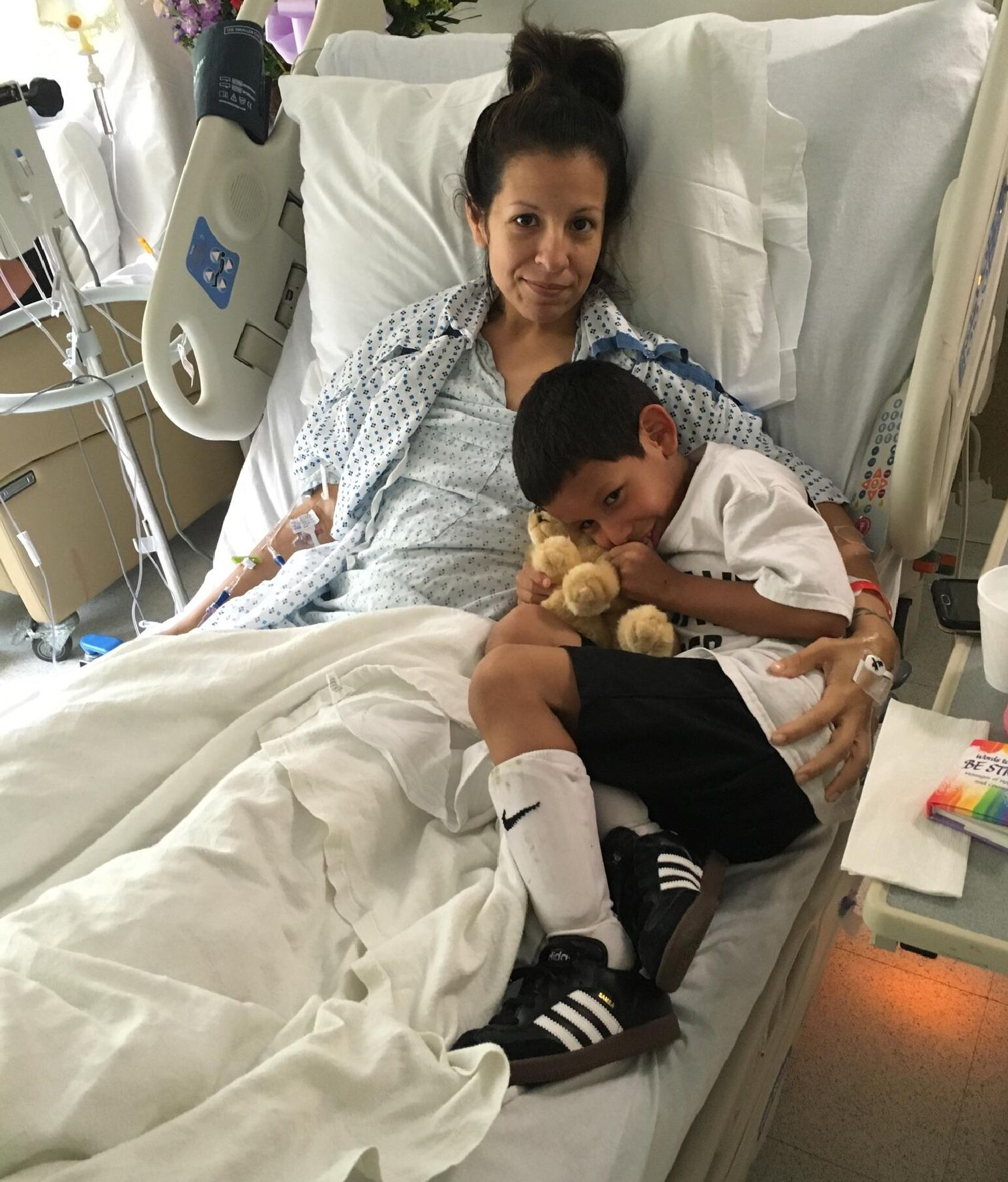 Mother recovering from colon cancer surgery in hospital bed with son