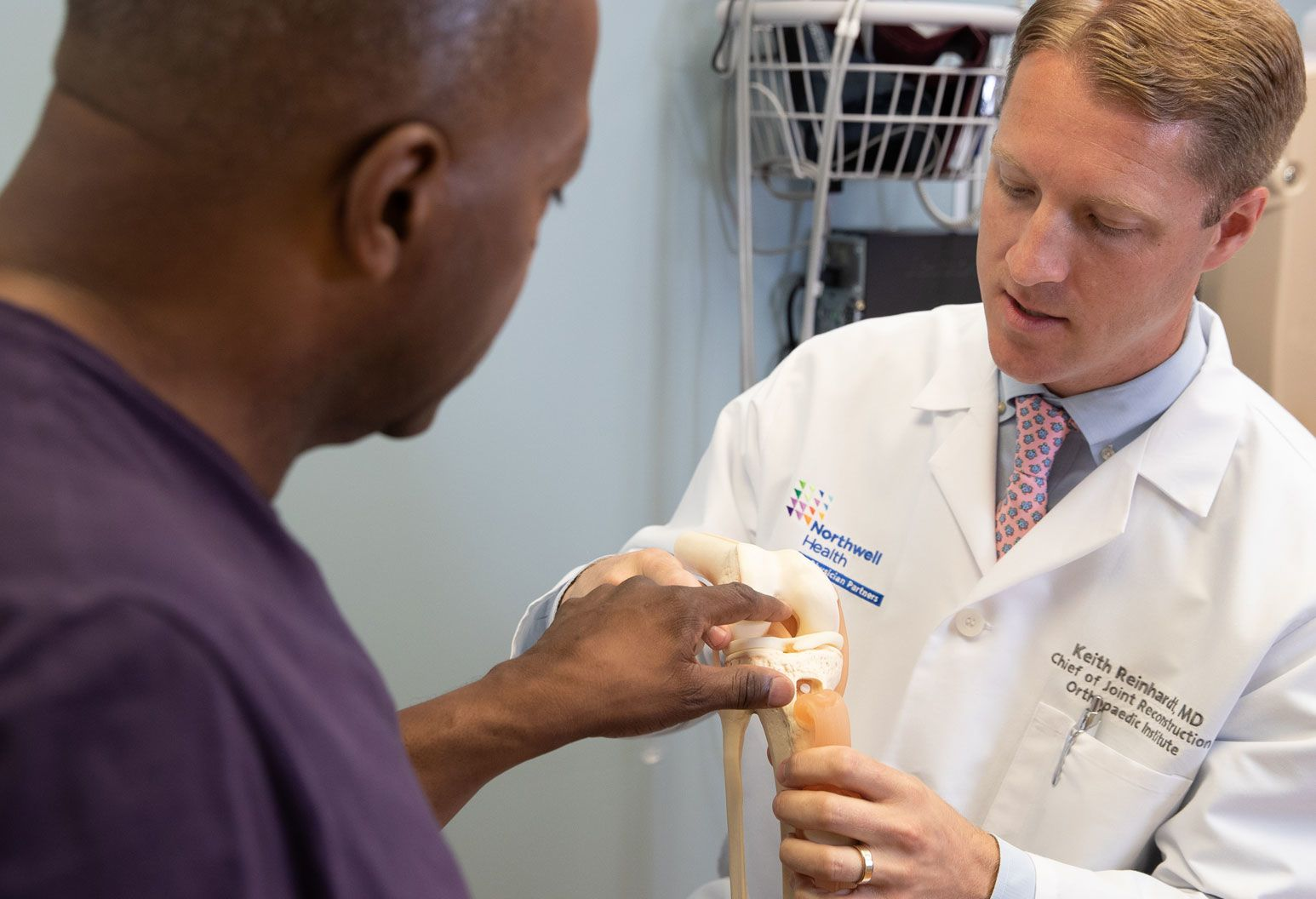 A doctor shows a patient a model of a joint, explaining a procedure.