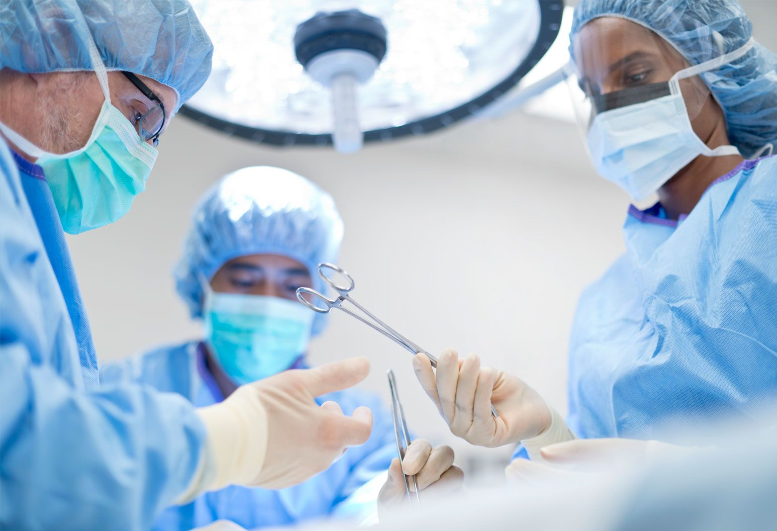 Three doctors wearing surgical gowns, masks, and gloves, are in an operating room standing over a patient as they perform surgery