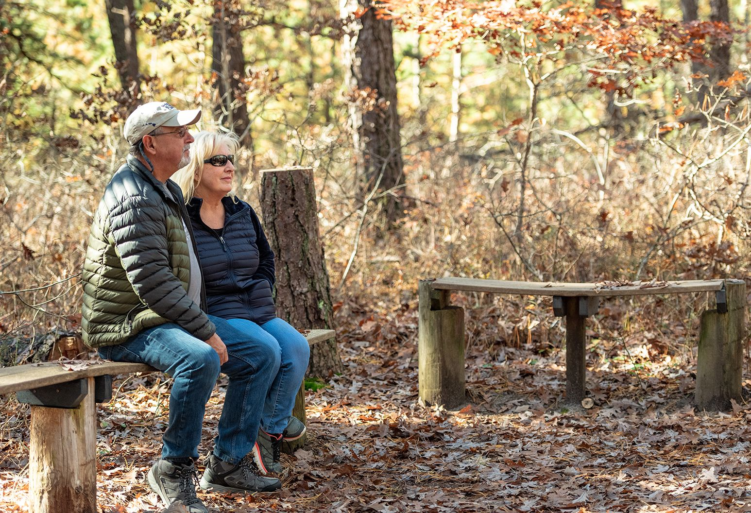 A married couple in their 60's sits on a bench outside and enjoys the quaint beauty of nature.